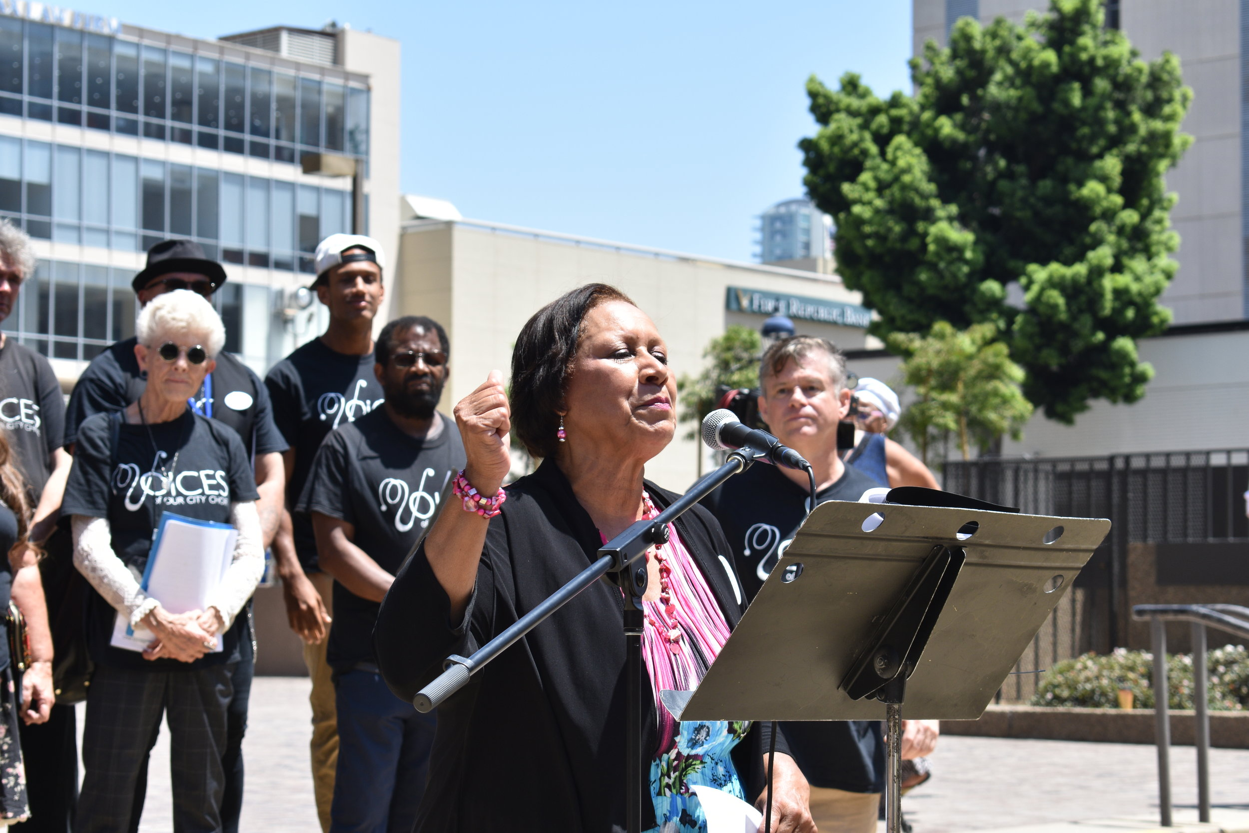 Jo Barrett, John Brady, and Voices of Our City Choir speaking before the rally, July 2019