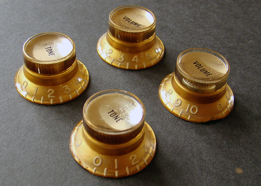 GOLD TIN KNOBS  These are a matched set of four 'tin tops', in excellent condition. No cracks or repairs. Taller knurl makes them suitable for 1961-1968 instruments. This set knobs have the gold tinted tops.  Price: POA