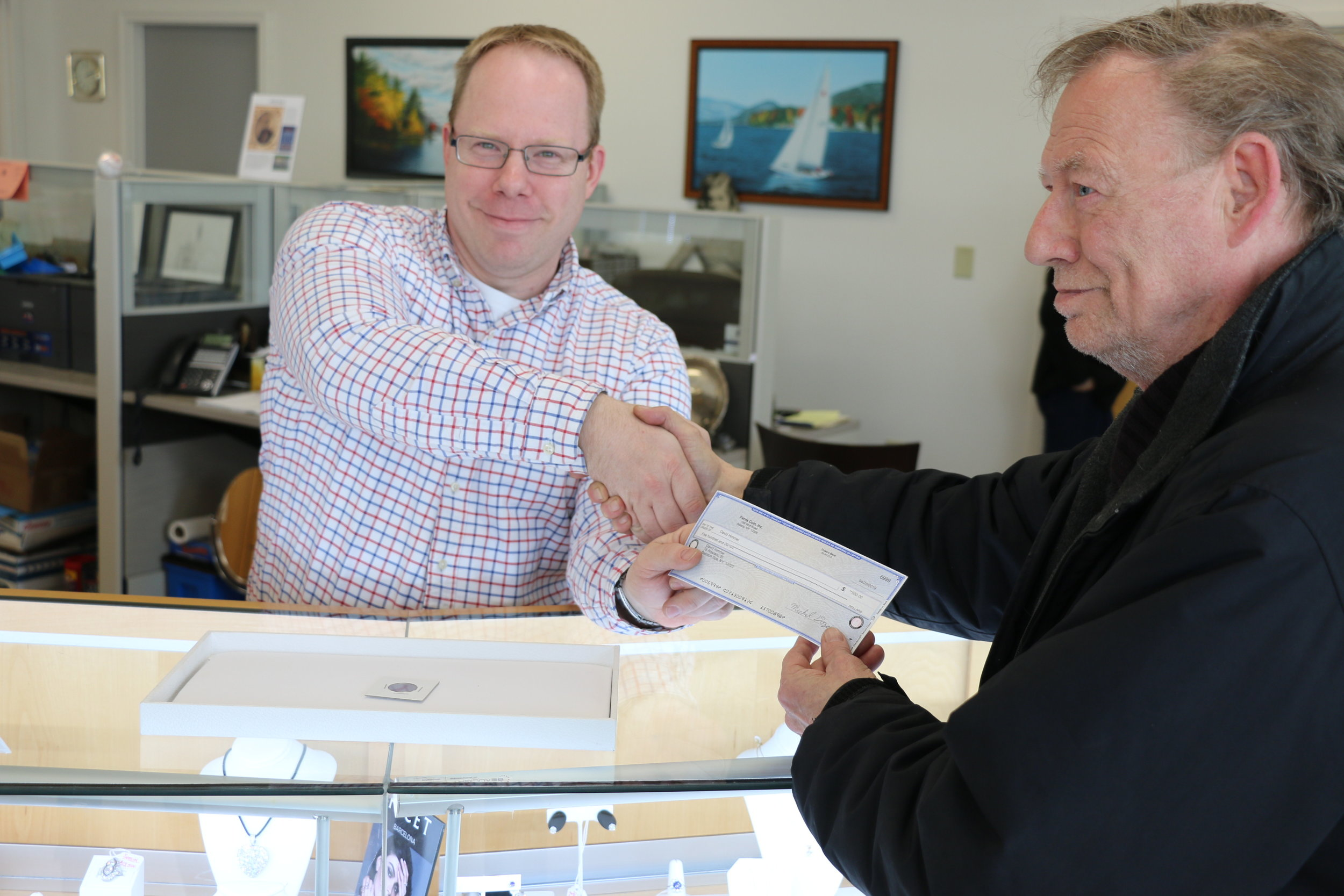 Ferris Coin & Jewlery Co. Managing Partner Mike Dozois hands David Himmel of Ballston Spa, N.Y. a check for $500 in exchange for his 2019-W Quarter.