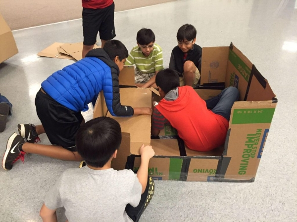 Students building a cardboard boat that has to support their teacher.