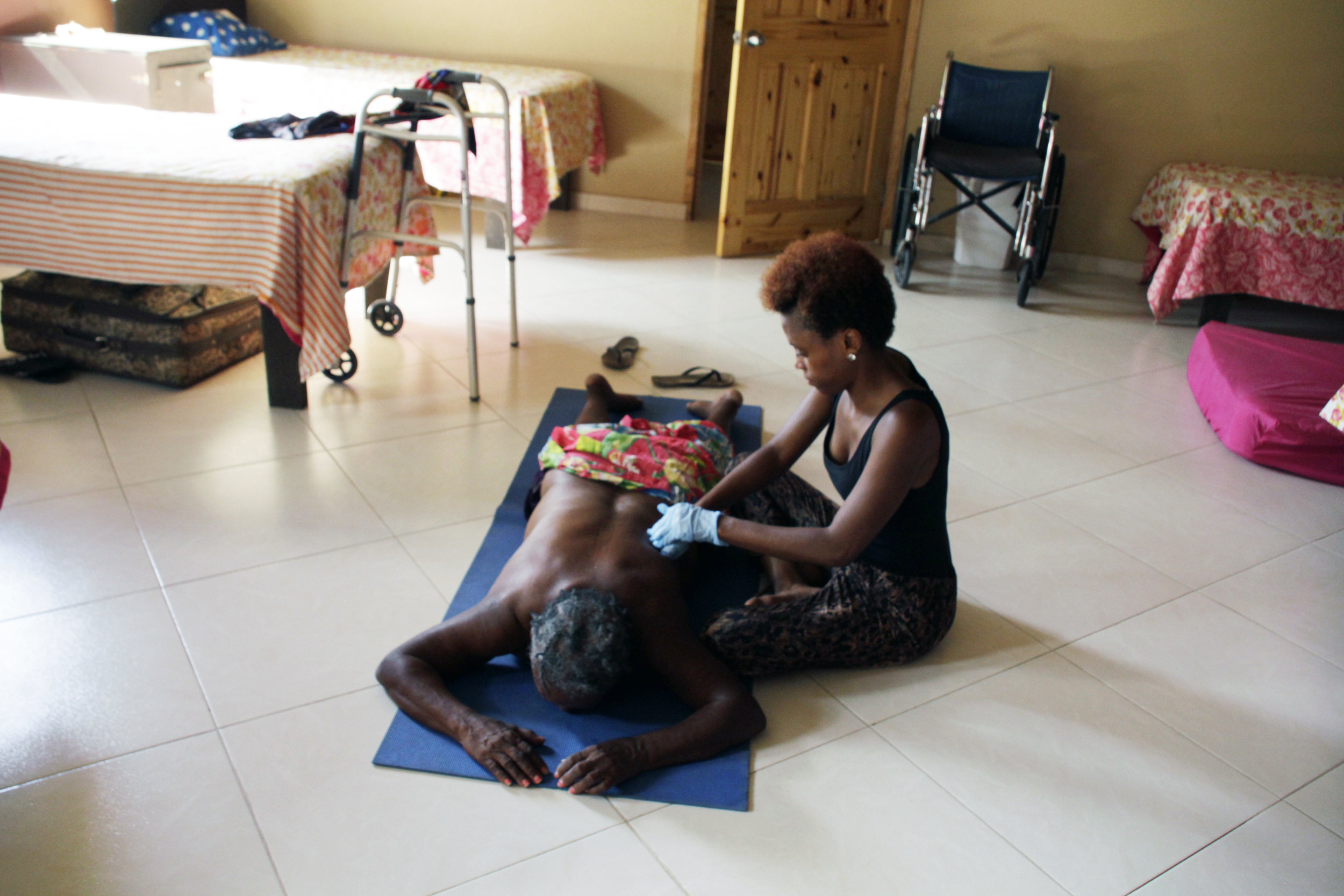 Pictured: 6 Month Intern, Carine Dorlus providing Physical Therapy to one of the Grandmas at the Home of Grace Elderly Home in Carries, Haiti. Home of Grace Elderly Home is a ministry of Mission of Grace. Carine completed her 6 month internship and the following semester graduated from Penn State University. Carine now serves as an advocate and translator for ATL4Haiti.