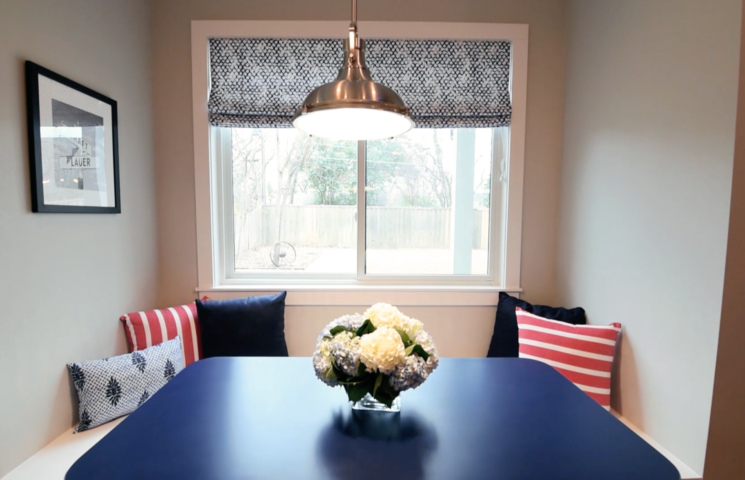 Breakfast nook with all of the cozy punches of color and the coolest retro diner table.