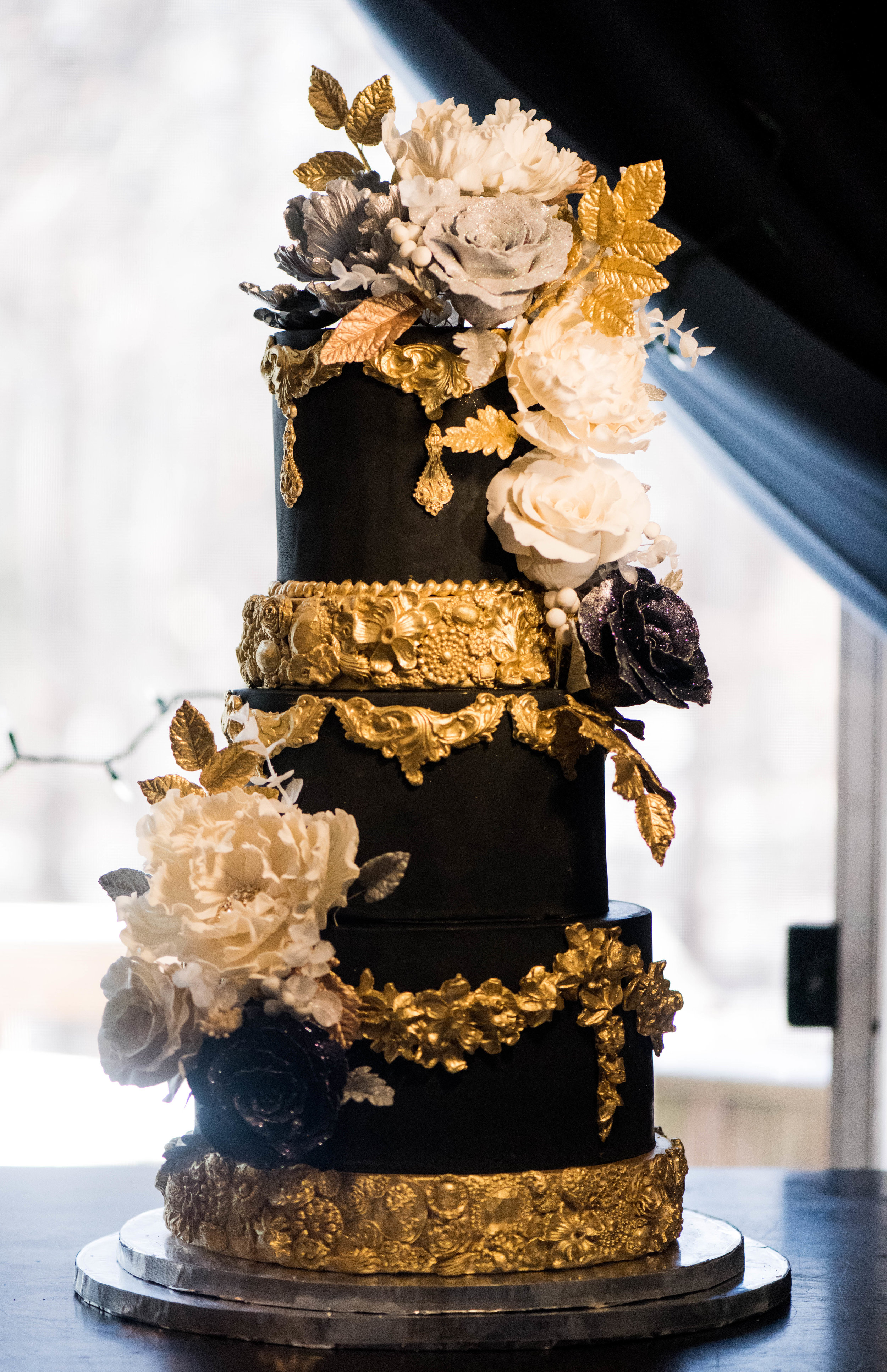 Ebony Elegance - This all black cake was paired with gold bas-relief effect tiers and ornate gold details. White, silver, and black sugar flowers add a romantic touch.