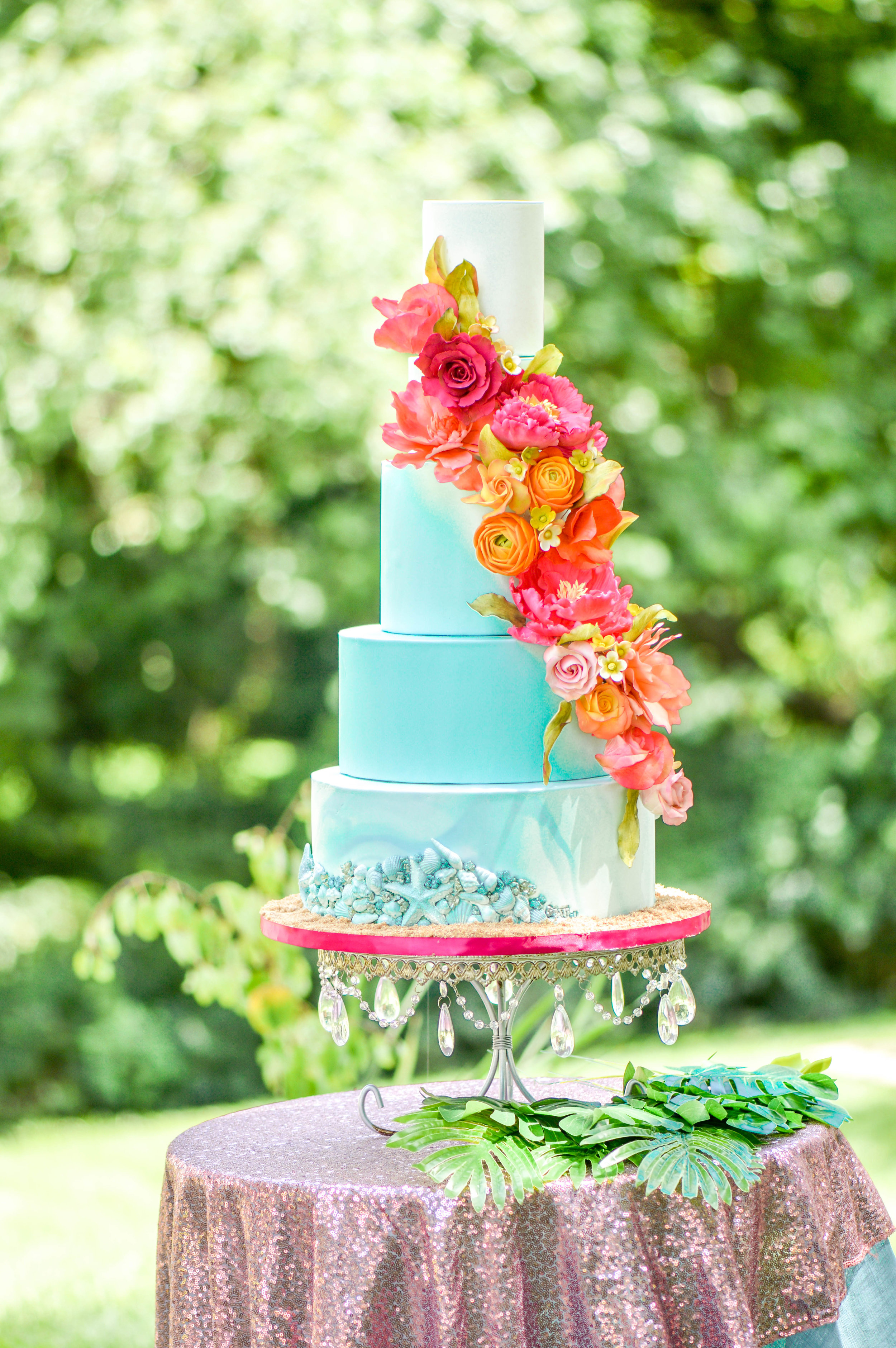 The cake featured bold and colorful sugar flowers and an ocean-blue canvas. -