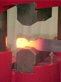 Drawing or lengthening a piece is achieved by repeated blows and turning the stock. The combination dies will move material the fastest for this operation. The narrow section will pinch and force the material perpendicular to the die. The flat area will smooth out the hammer marks of the fullering area. Clamping a taper block on the flat area can form tapers. A 5/8-inch tapped hole on the right side of the machine is used to hold this type of tooling. -