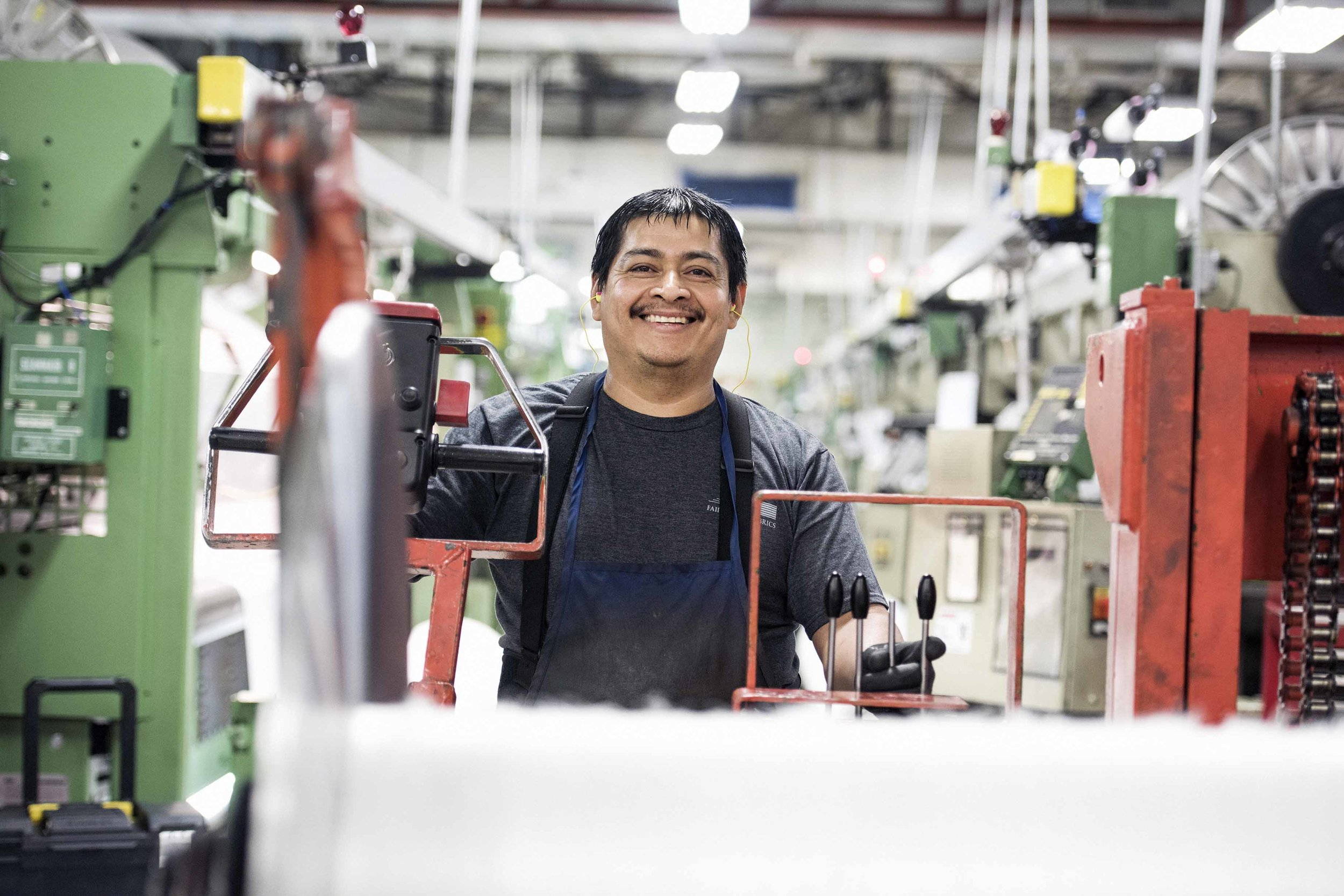 Fairystone Fabrics employee smiling near machinery