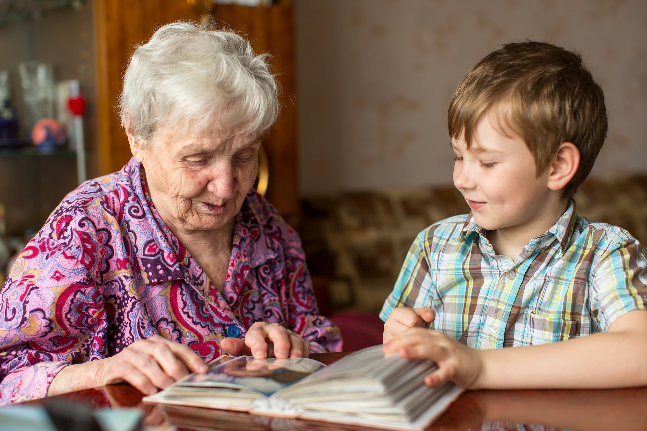 Grandmother and boy look at a photo album