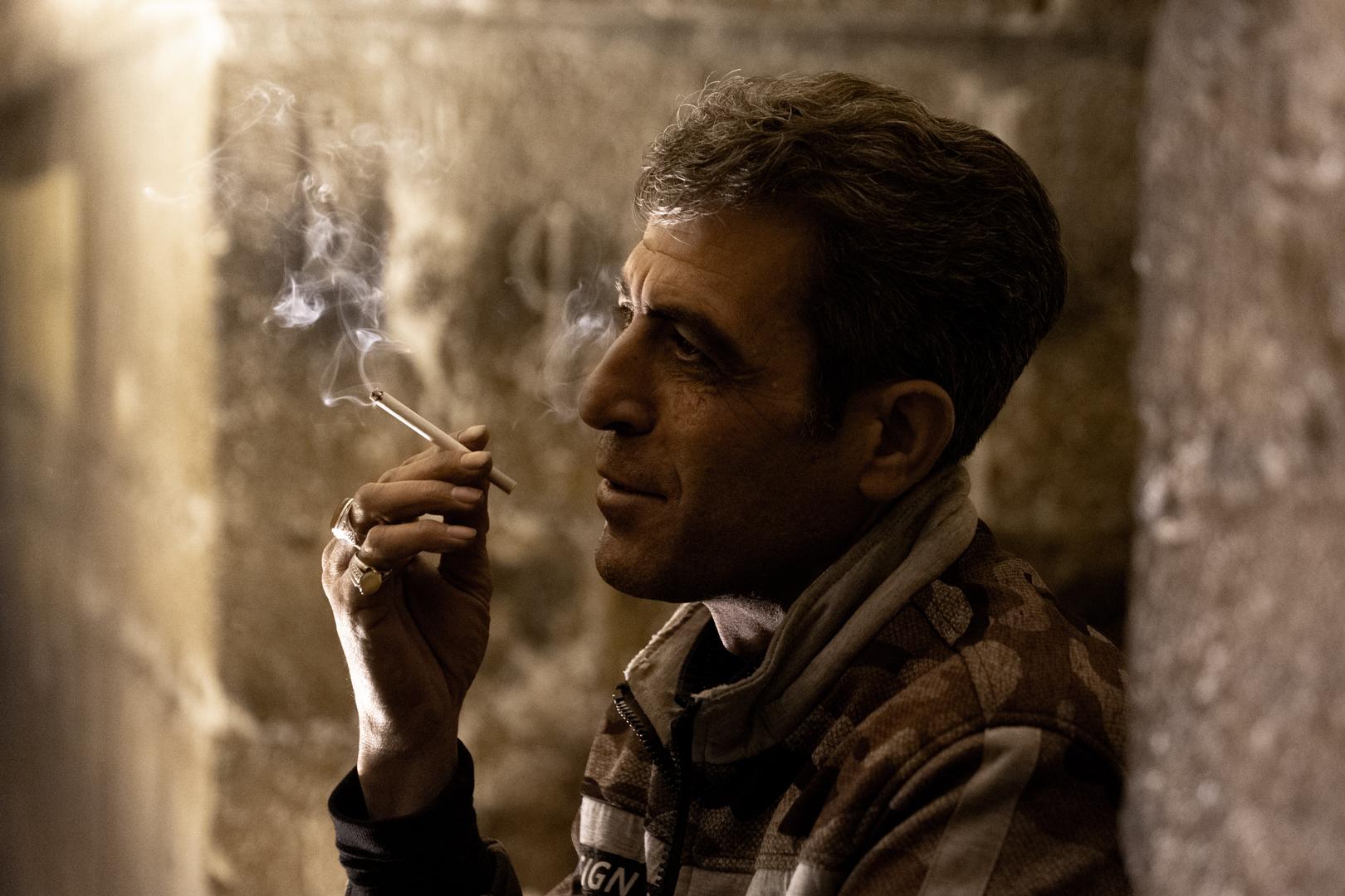 A man enjoying his cigerette, watching the show of performers under the Khaju bridge, Isfahan, Iran