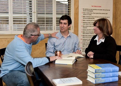 A young man discusses recovery with his parents