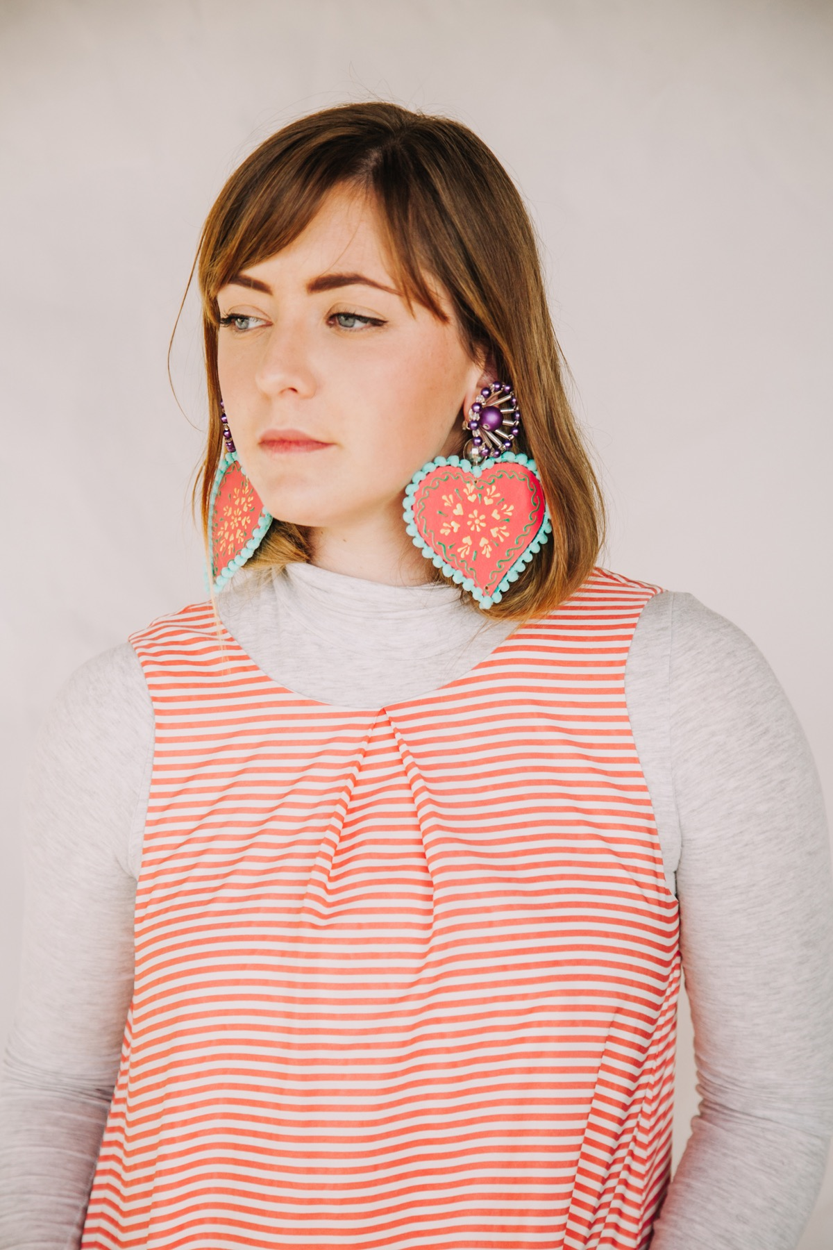 Painted - Wooden | SpoungyThese handpainted Indian decorations make the most tremendous earrings.Lined with fuzzy pom pom trim, they really are a feast for the senses.