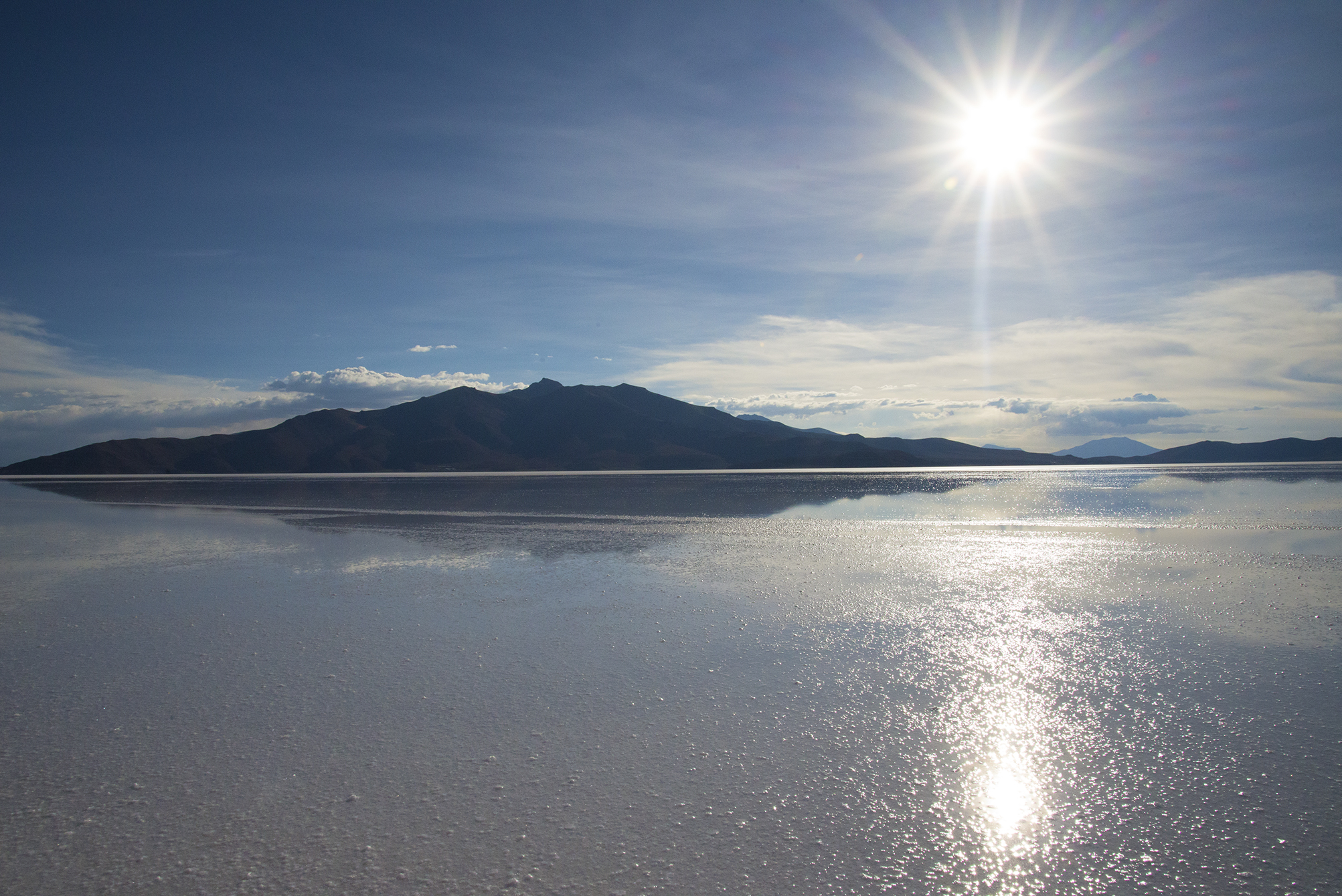 On a salar in Bolivia, wading through forming salt crystals in the water before the sun sets.