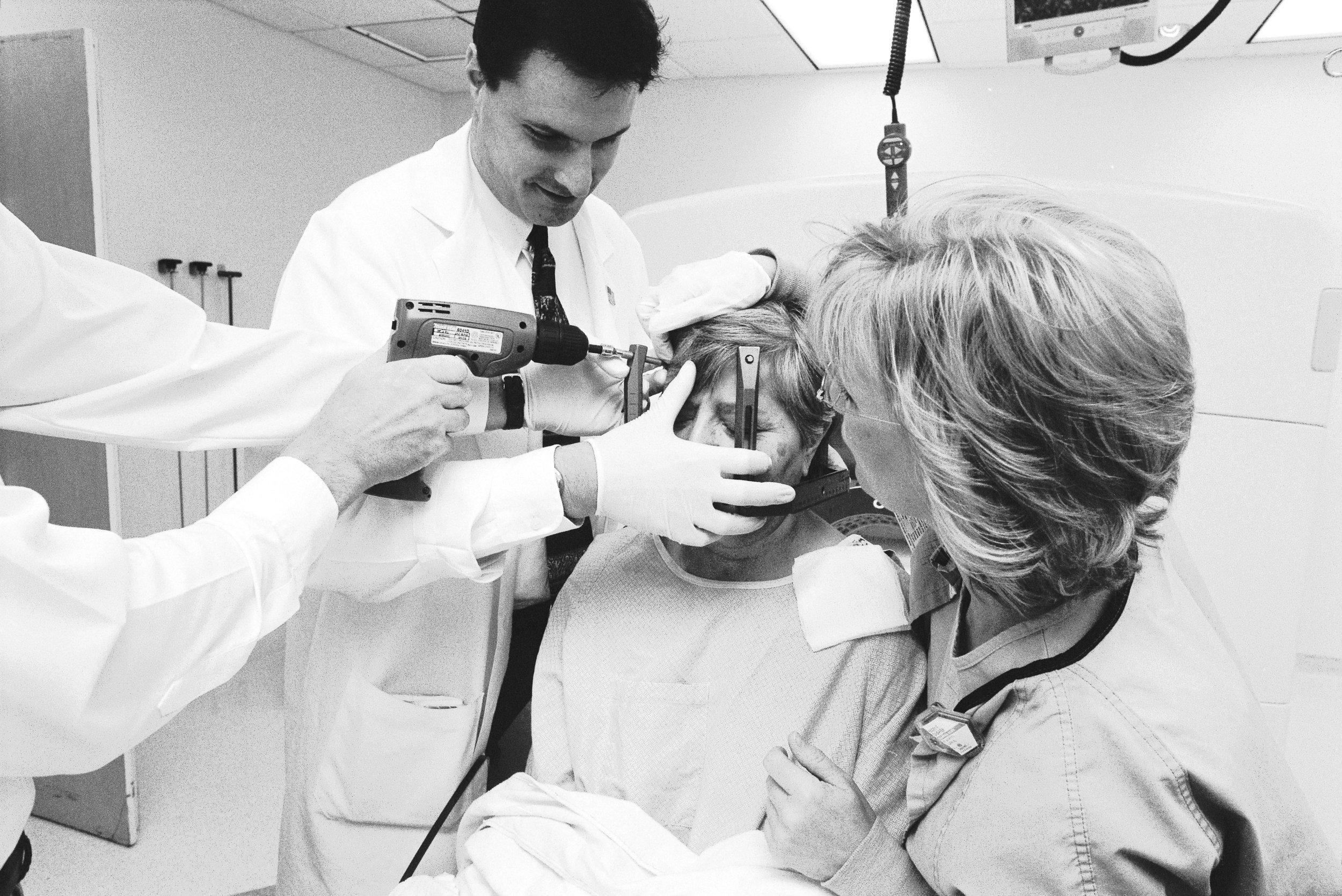 A patient having the frame removed from her head. Although it looks like the doctor is drilling the screws into the patient's head, he is actually using the drill to 'unscrew' the frame from her head.