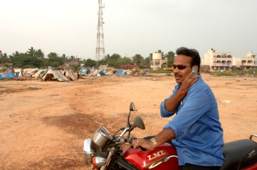 The gulf between the 'haves' and the 'have-nots'; is very noticeable in India. Here a man on his new motorbike makes a call in front of one of many rural slums on the outskirts of Chennai (Madras).