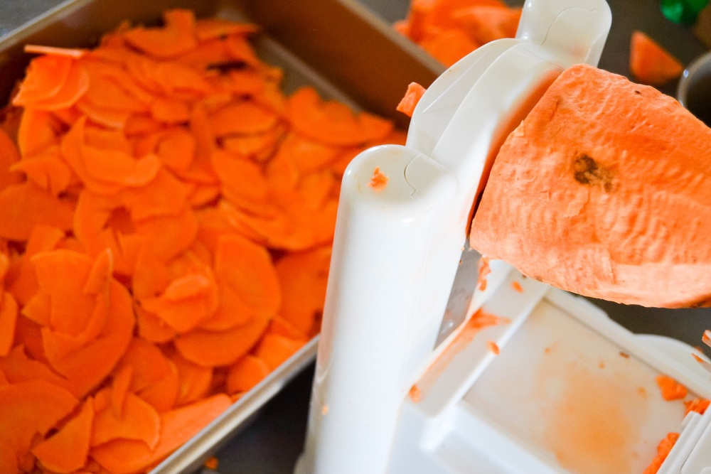 Using a spiral slicer to evenly and quickly slice the sweet potatoes