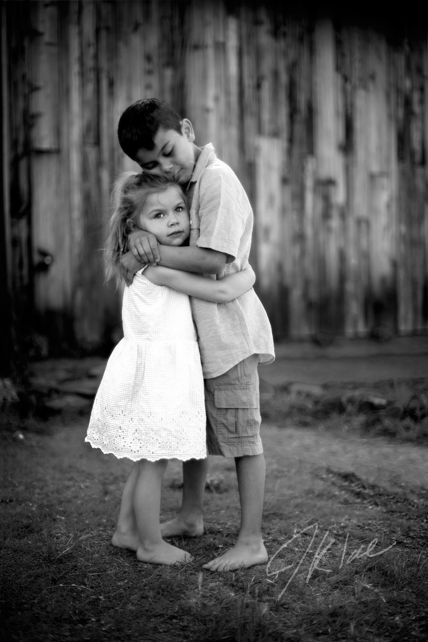 Frisco Texas Kids Photoshoot in Black and White with Brother and Sister hugging near barn