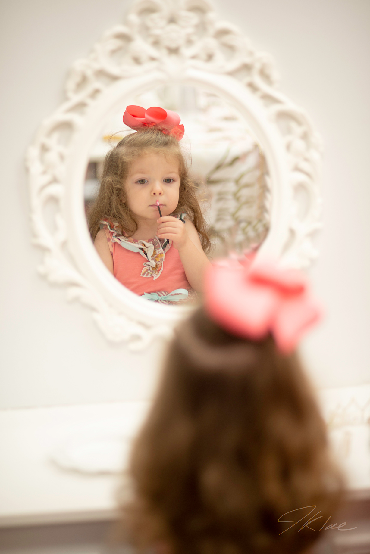 Princess Portrait of girl looking in mirror putting on gloss in Frisco Texas