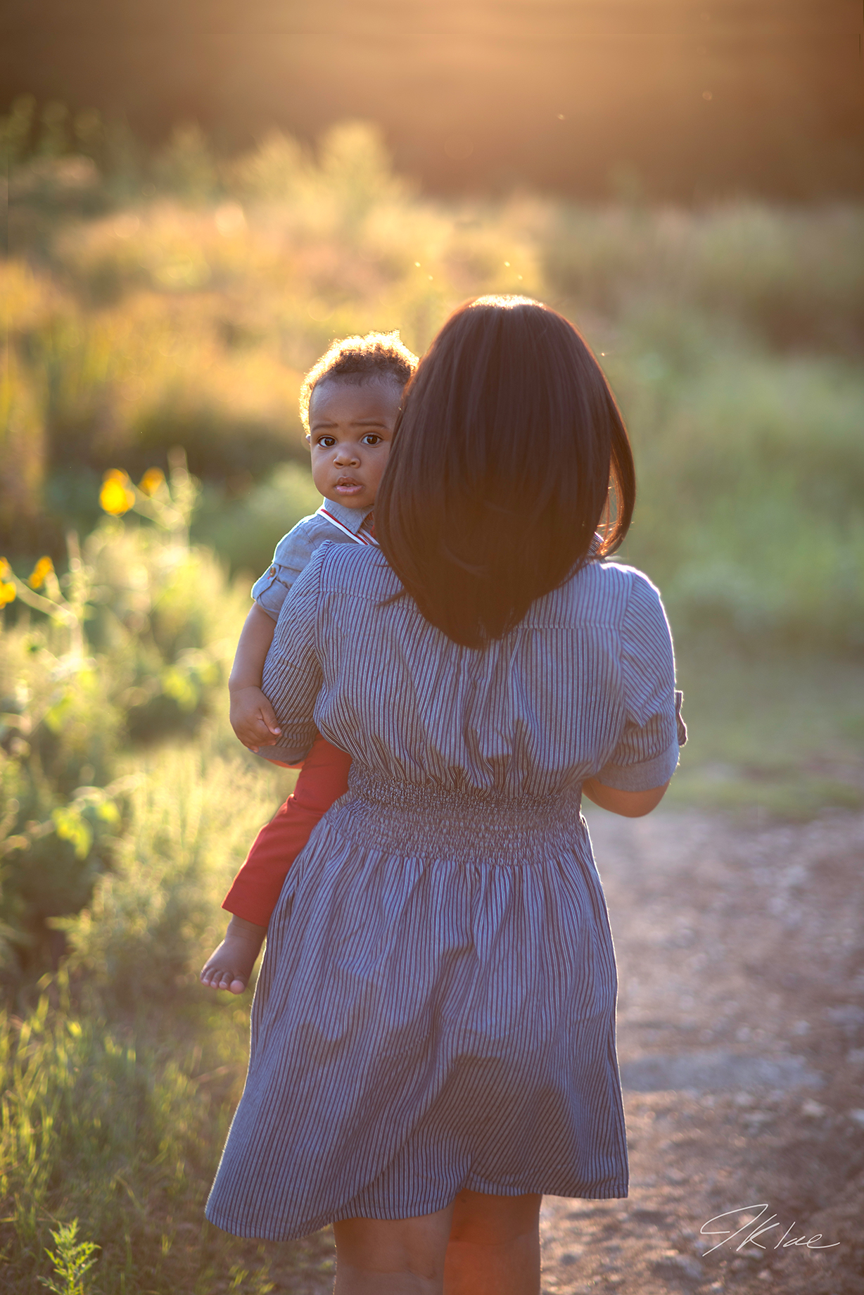 Family Portrait of Mother holding Son as he peers over shoulder at Arbor Hills Nature Preserve in Plano Texas