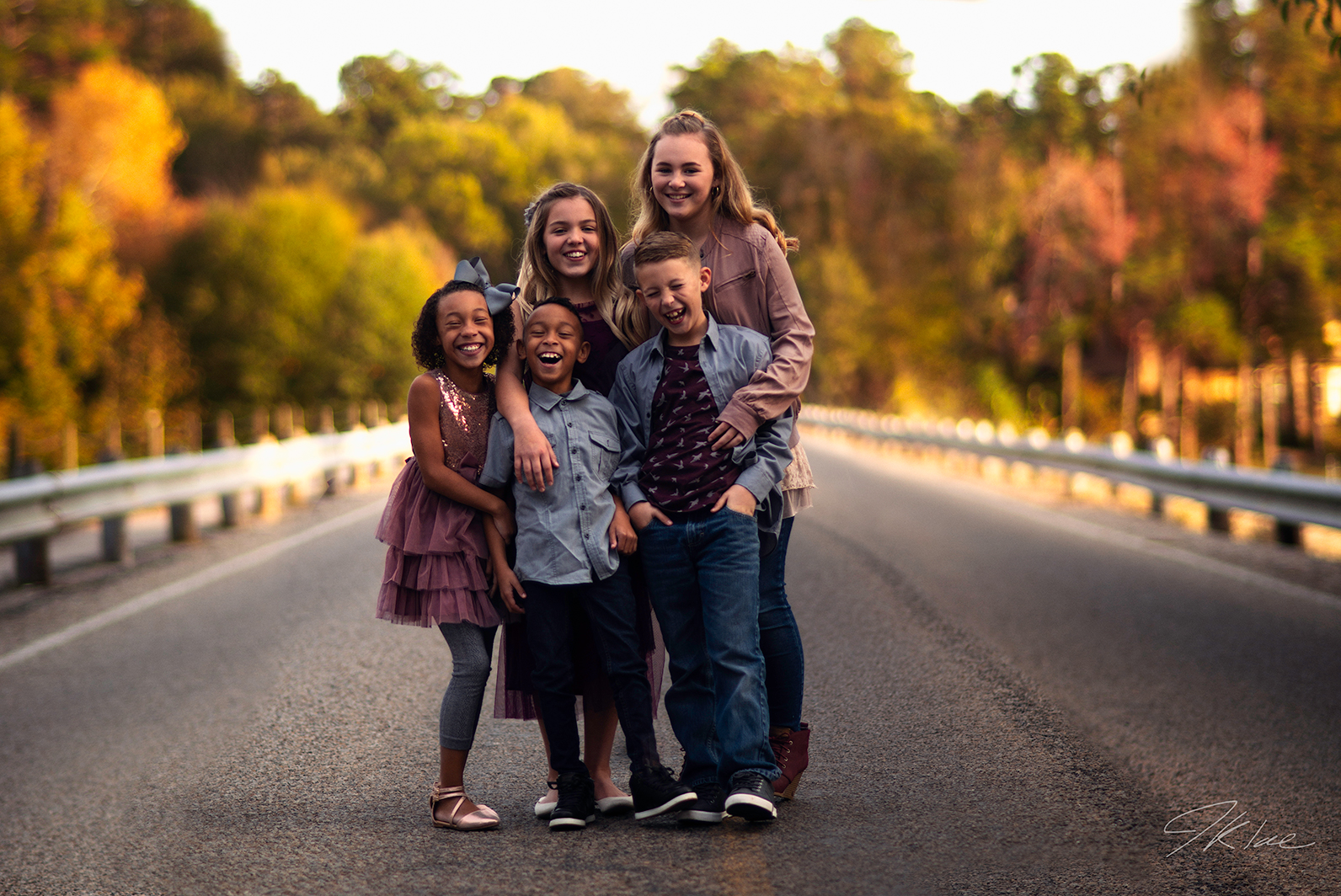 Kids Photoshoot with five siblings laughing on a bridge in Lindale Texas