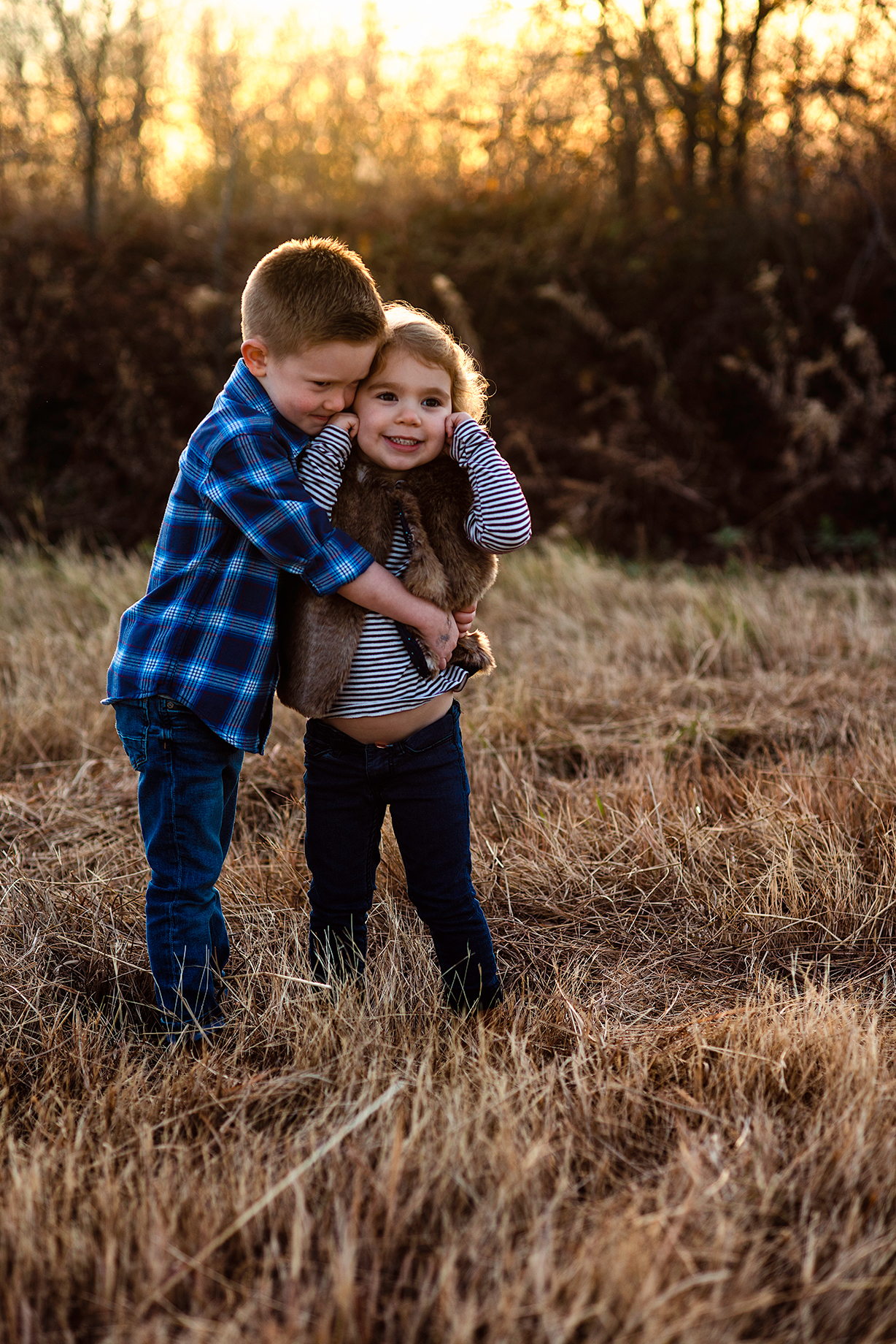 Toddler Photoshoot of Brother hugging Sister while she plugs her ears in McKinney Texas