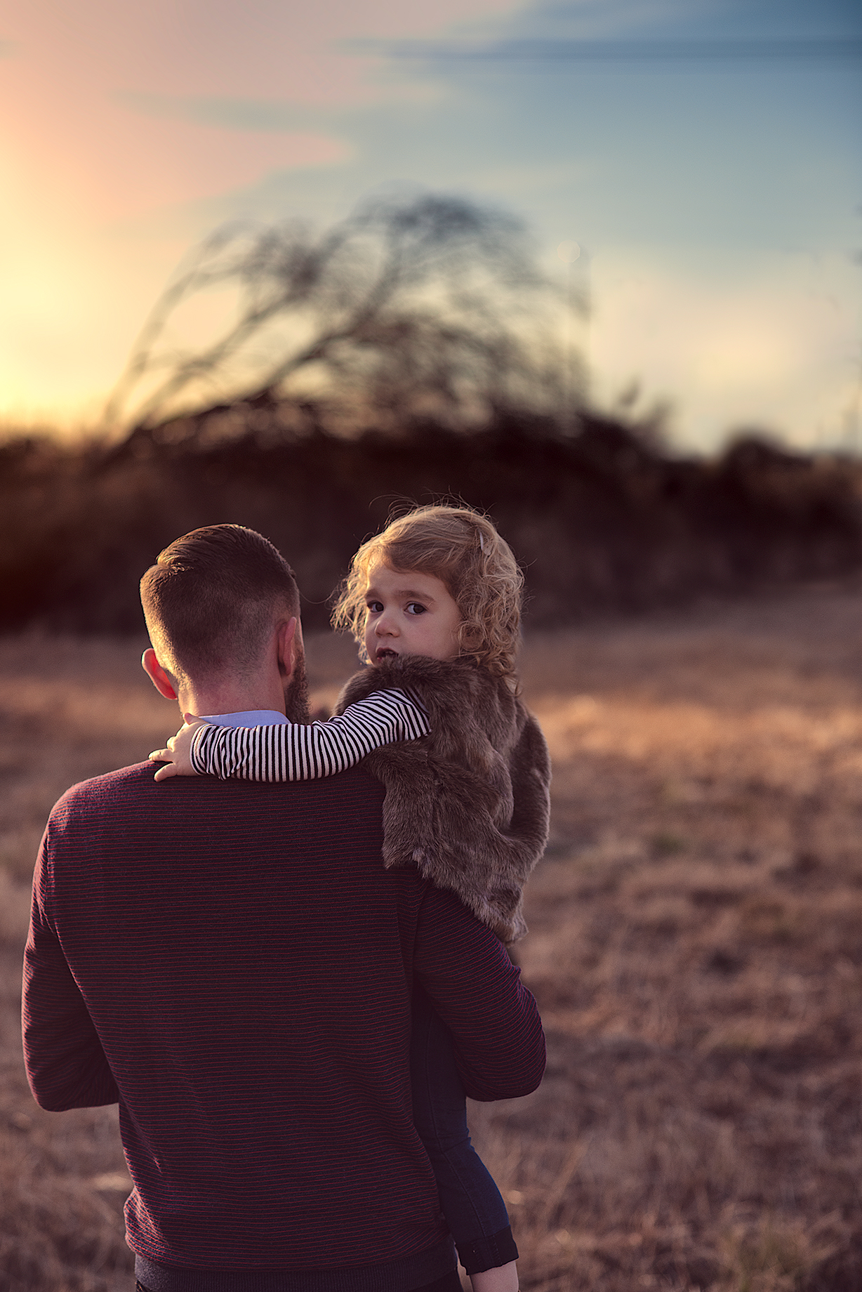 McKinney Texas Family Portrait during sunset of Father holding Daughter as she peers back over his shoulder