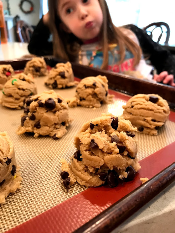 """Scoop the cookies out and place them on a parchment or silicone mat lined cookie sheet. Also, I love my daughter's expression here, she is doing exactly what I feel inside, """"Are the cookies ready yet?"""""""