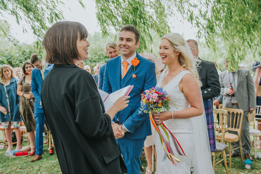 Cathy and Ste celebrating their humanist wedding outside at The Willow Tree, in Bourn. Image by Rebecca Watts Photography