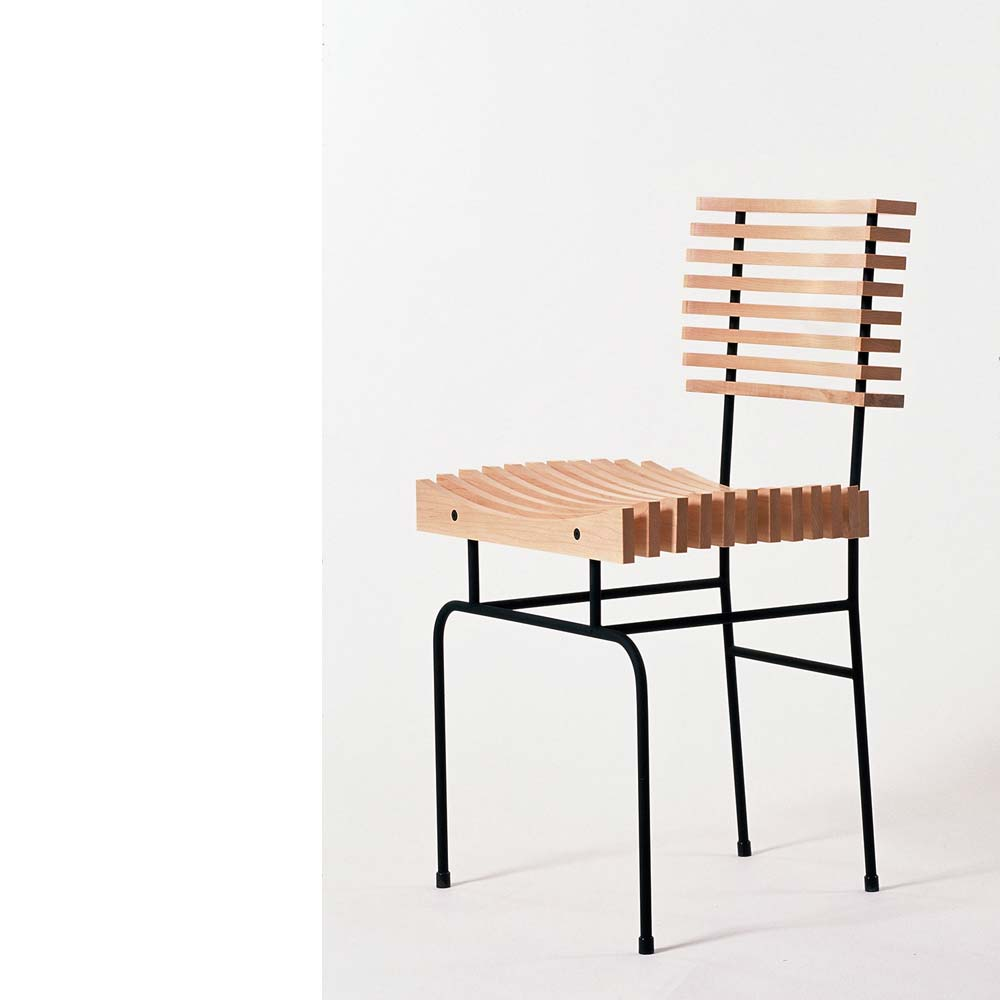 Concept - The slatted chair is designed for comfortable home or restaurant dining. The curve of each slat is the same, yet they are positioned on the chair frame to provide a double curve for both the back and seat of the chair. The double curve supports the back comfortably and the double seat curve is sprung using nylon seat bars to adapt to the shape of the diner, giving a very comfortable seating experience.The slatted chair was shown at the New Designers in Business and Going Solo exhibitions in London in 1997, after which an edition of 25 chairs were made. The chair has also been displayed in the 'chair alley' of the London Design Museum.