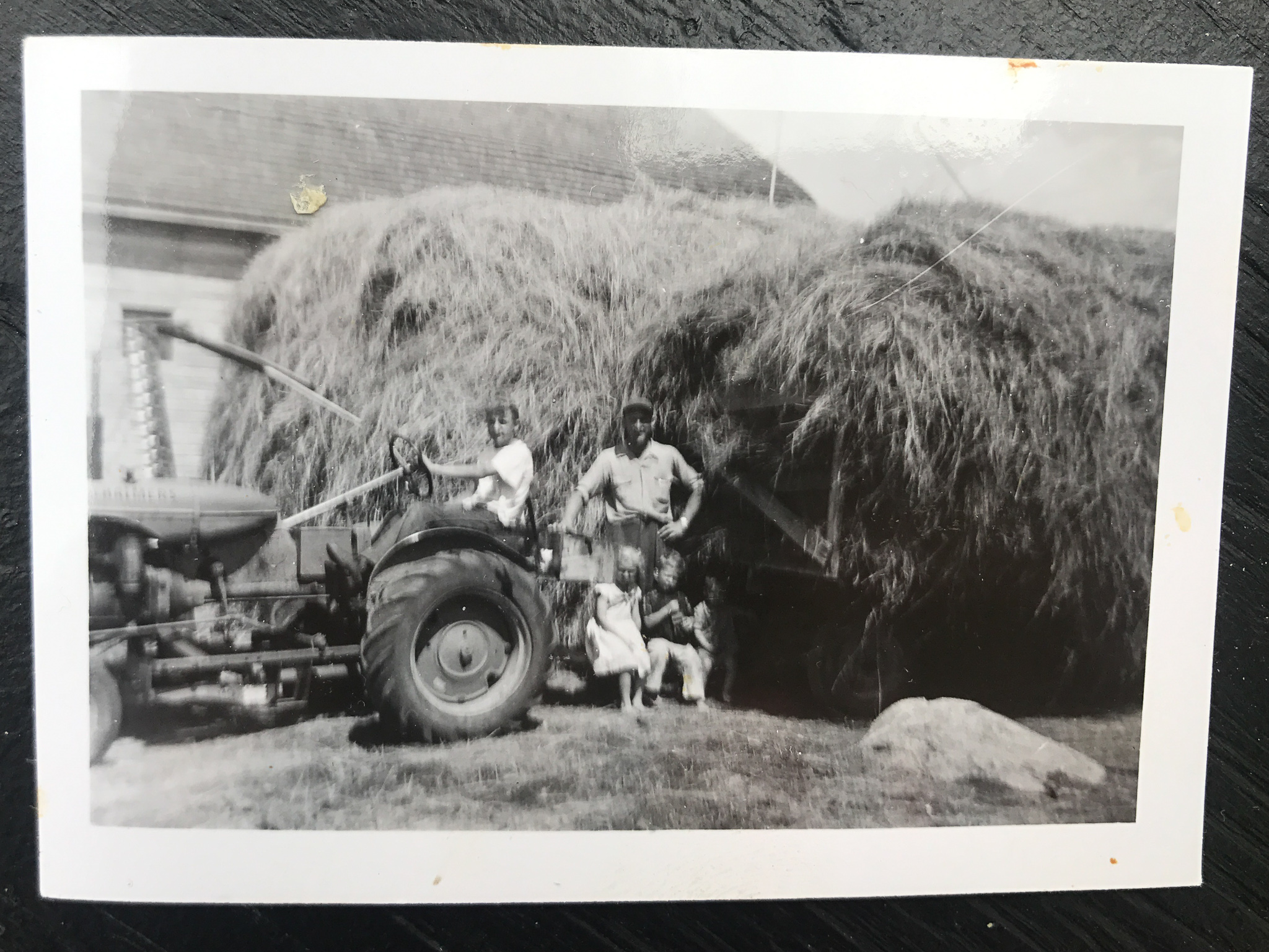 Young hired help on tractor, Louis with his children Diane, Gérald and Claude (1960's)