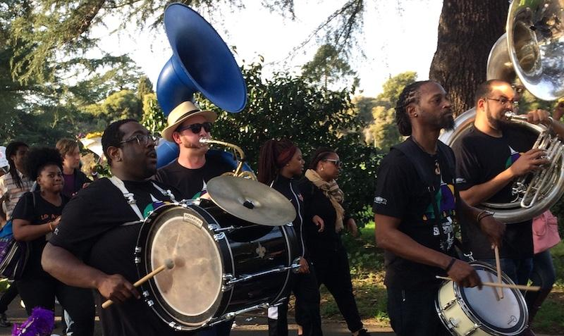 Nate Cameron (left) plays his drum while marching through the crowd.    JENEE DARDEN / KALW NEWS