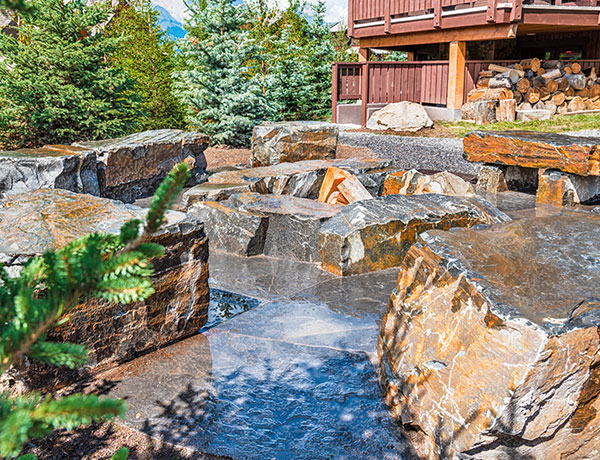 A backyard featuring retaining walls and water features in the Calgary and Banff area