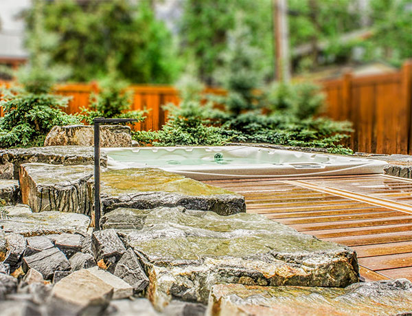 A wooden deck complete with a hot tub in the Calgary and Banff area
