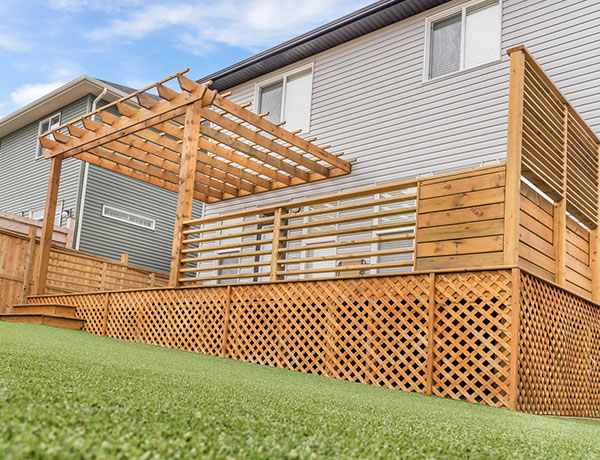 A wooden outdoor enclosure positioned against the side of a house in the Calgary and Banff area
