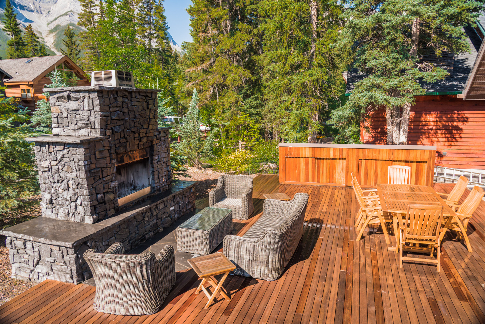 A custom masonry fireplace with rundle stone and composite decking in the Calgary and Banff area