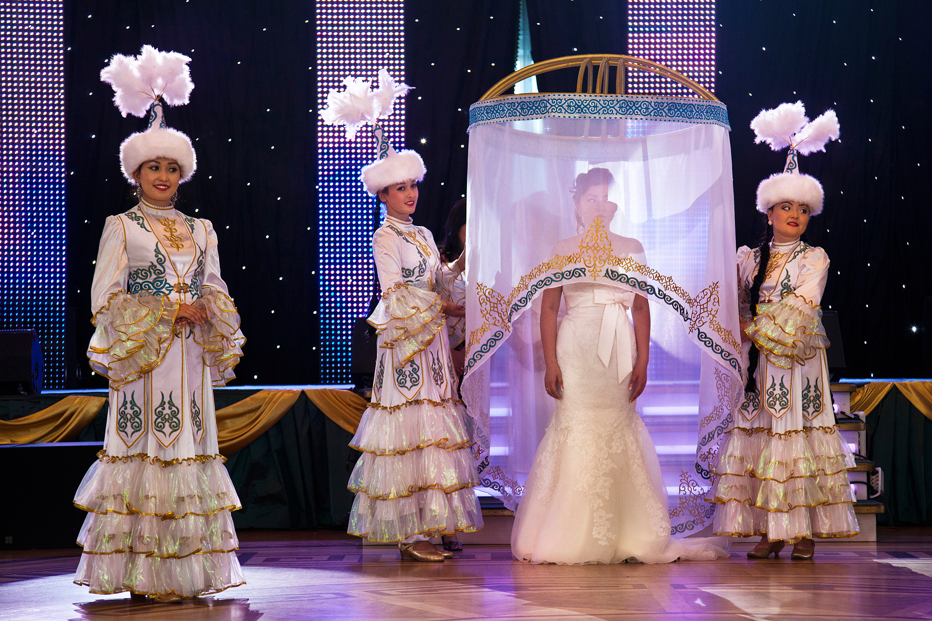 Flanked by traditional Kazakh dancers, a bride awaits her formal unveiling at an opulent wedding palace, where she has just been married in a ceremony capped by the release of two white doves. The revelry begins when the veil is lifted.  Astana, Kazakhstan
