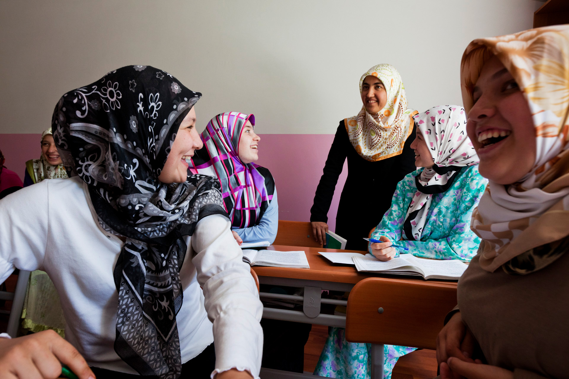 Eleventh grade Tatar girls giggle because of their female teacher's Turkish accent during their religious lessons.  Azovskoye, Crimea