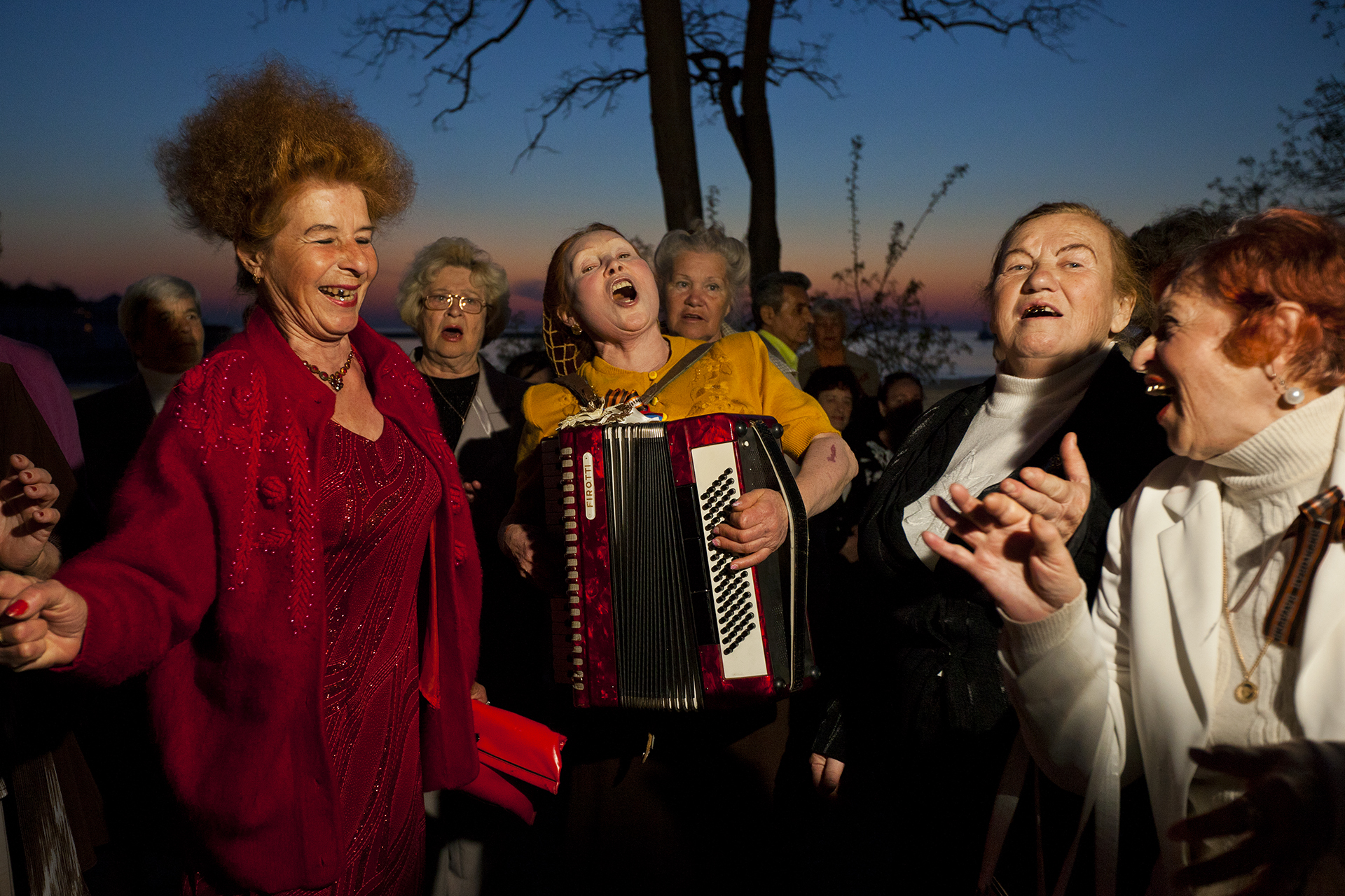 Chords of friendship bind accordionist Olesya Kamovich and comrades, who meet Sundays in Sevastopol on the promenade to sing and dance into the early night.  Sevastopol, Crimea