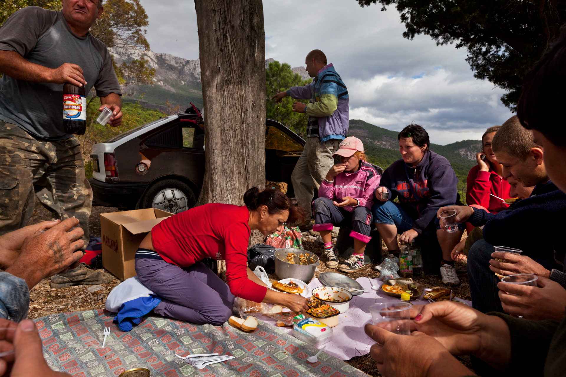 A group of hired grape pickers break for a bucolic lunch in the vineyards near the Crimean coastline.  Near Yalta, Crimea