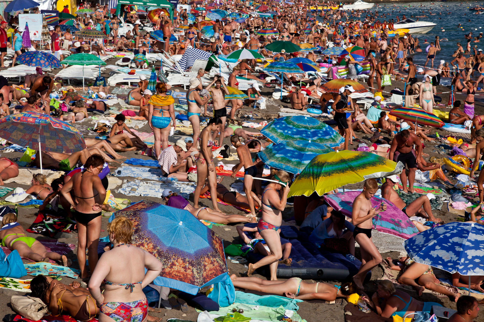 Sun, sand and sea are the payoffs for six million tourists a year who crowd like this one in Sudak.  Sudak, Crimea