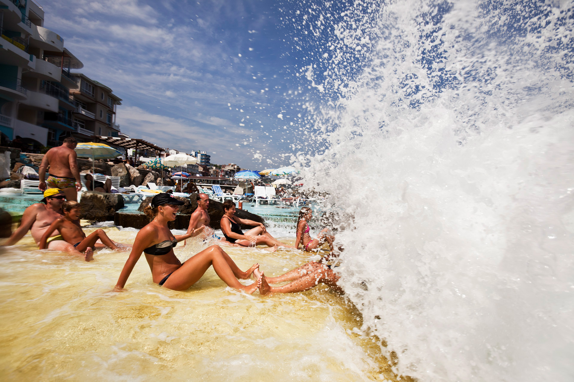 A giant wave splashes sunbathers on the Santa Barbara beach, a picturesque strip along a marvelous coastline with rocks and stone, popular among young upper middle-class families with children.  Utes, Crimea