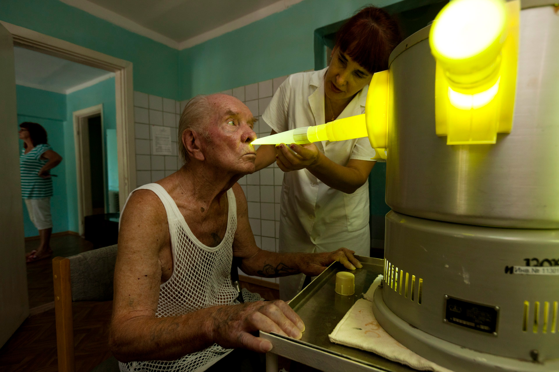 A specialist at the Veteran Santorium in Alushta assists an ailing patient with the inhaler, used to treat respiratory diseases. Patients at this state-owned sanatorium are the beneficiaries of what's left of a Soviet system that ensured each citizen a paid vacation, subsidized spa treatments, and free health care.  Alushta, Crimea