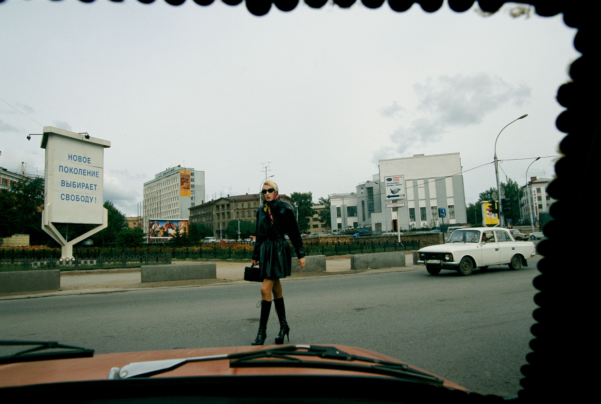 "View on the New Russia: A car's windshield, held in place by coins, frames a woman dressed to kill and a roadside sign reading, ""the new generation chooses freedom.""  Novosibirsk, Russia"