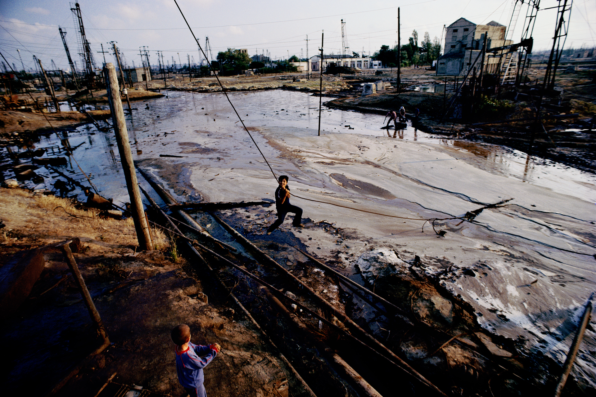 Children play in the inky pools of runoff from leaky oil pumps. Azerbaijan's fields lost prominence when oil exploration shifted to Siberia in the 1960s.  Baku, Azerbaijan