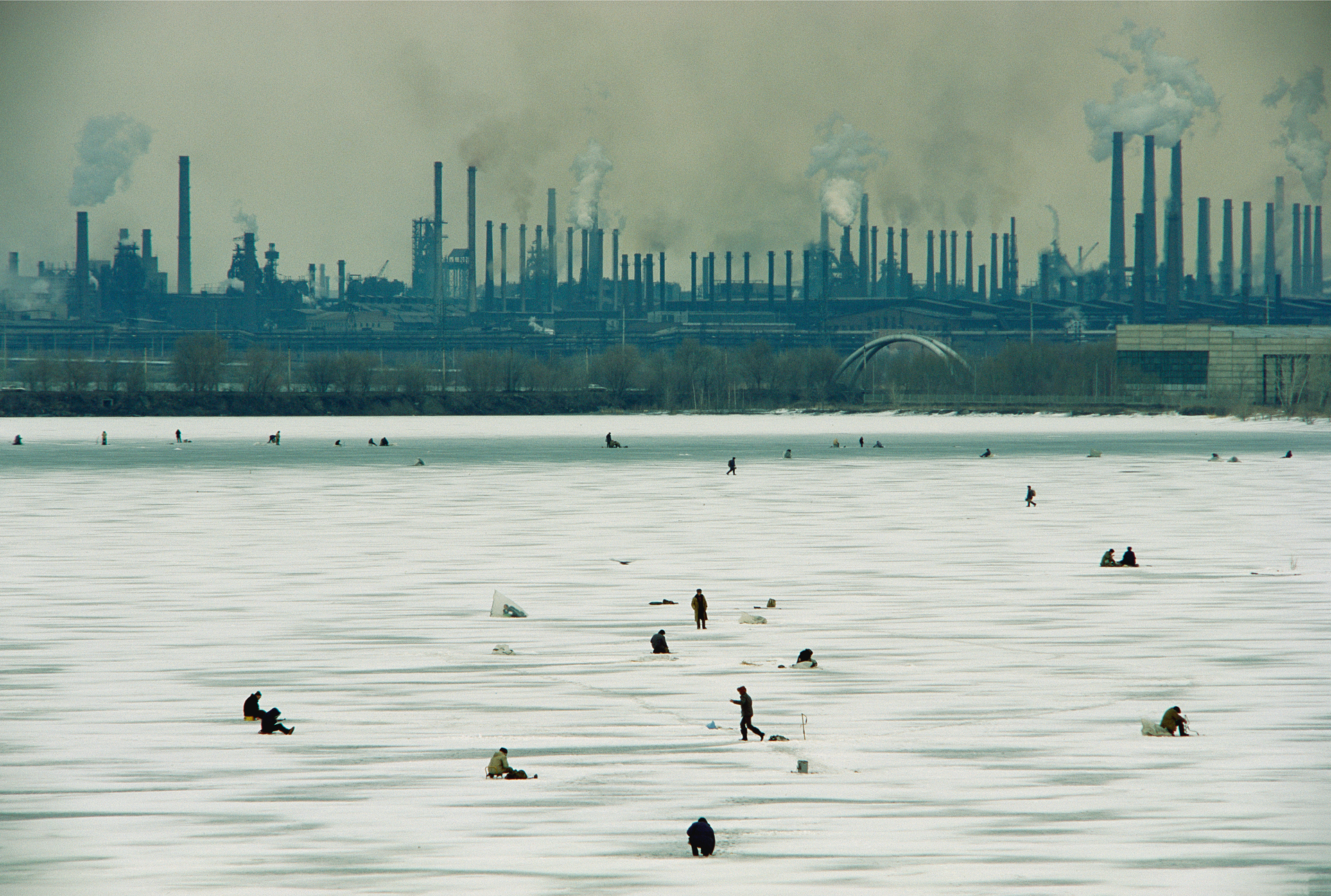 In winter, men drill fishing holes in the ice of the Ural River. Knowing that the river is badly polluted by the Steel Works looming behind them, they often sell their catch to markets rather than consume it themselves.  Magnitogorsk, Russia