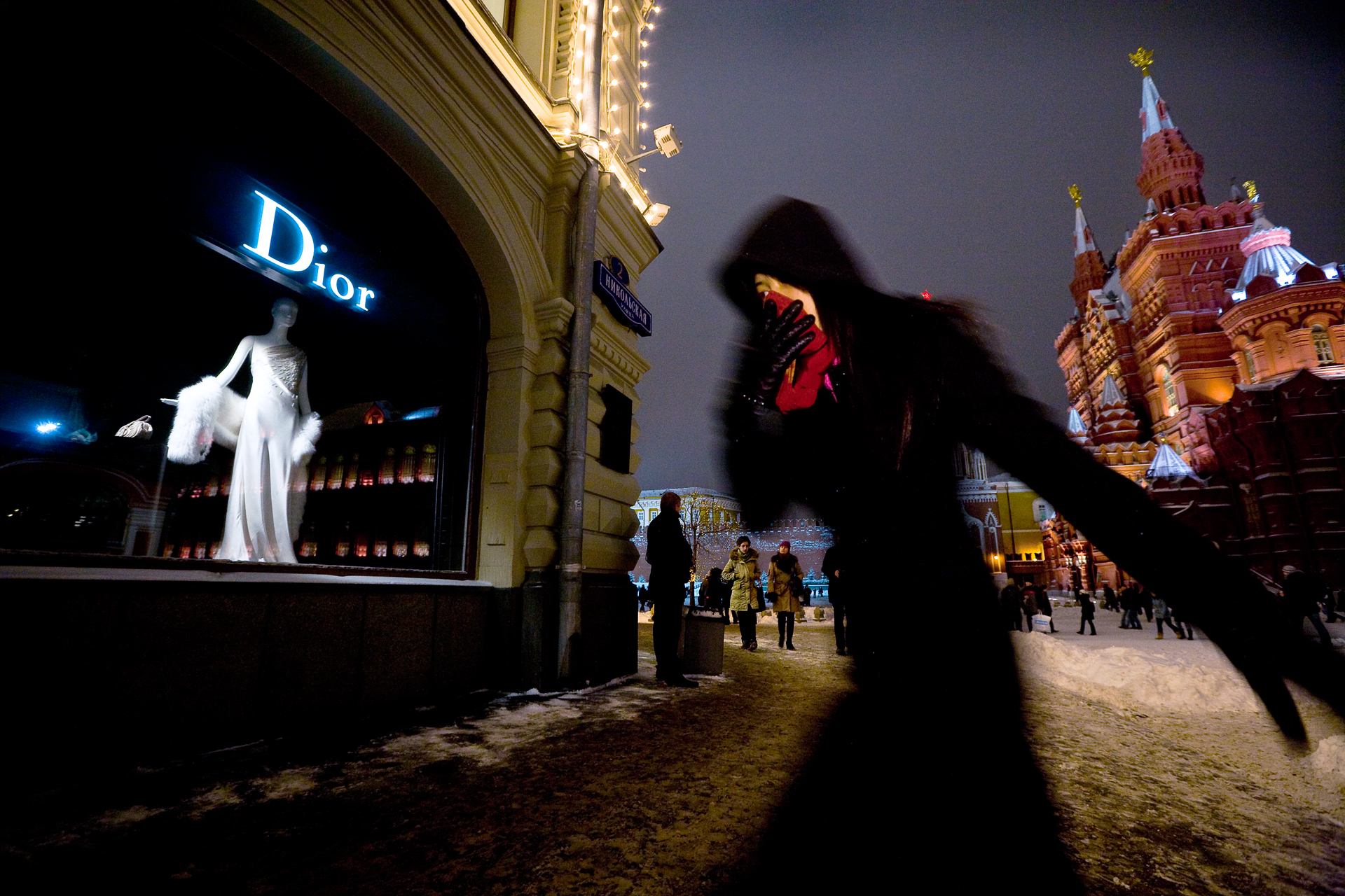 6:01PM - A shopper scythes through bitter cold to reach a boutique on Red Square. These materialistic days, Marx and Lenin can't compete with Dior and Armani for the hearts of the consuming class.
