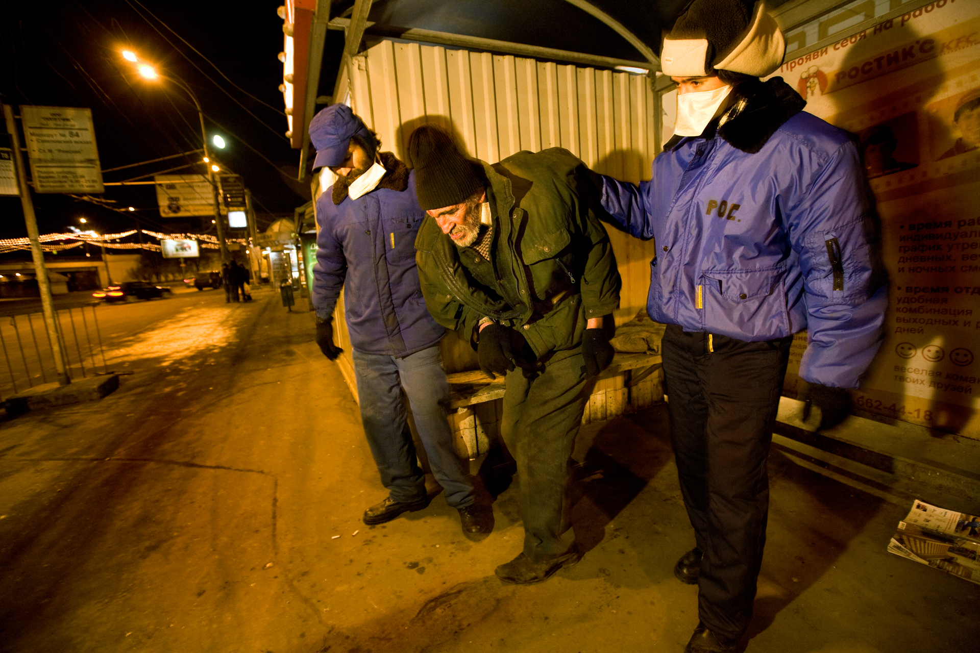 11:46 PM - Volunteers guide an old homeless man towards a Soviet-era bus used as a mobile clinic, and during extremely cold nights like this one (-15° C), to keep the homeless from freezing to death on the city streets.