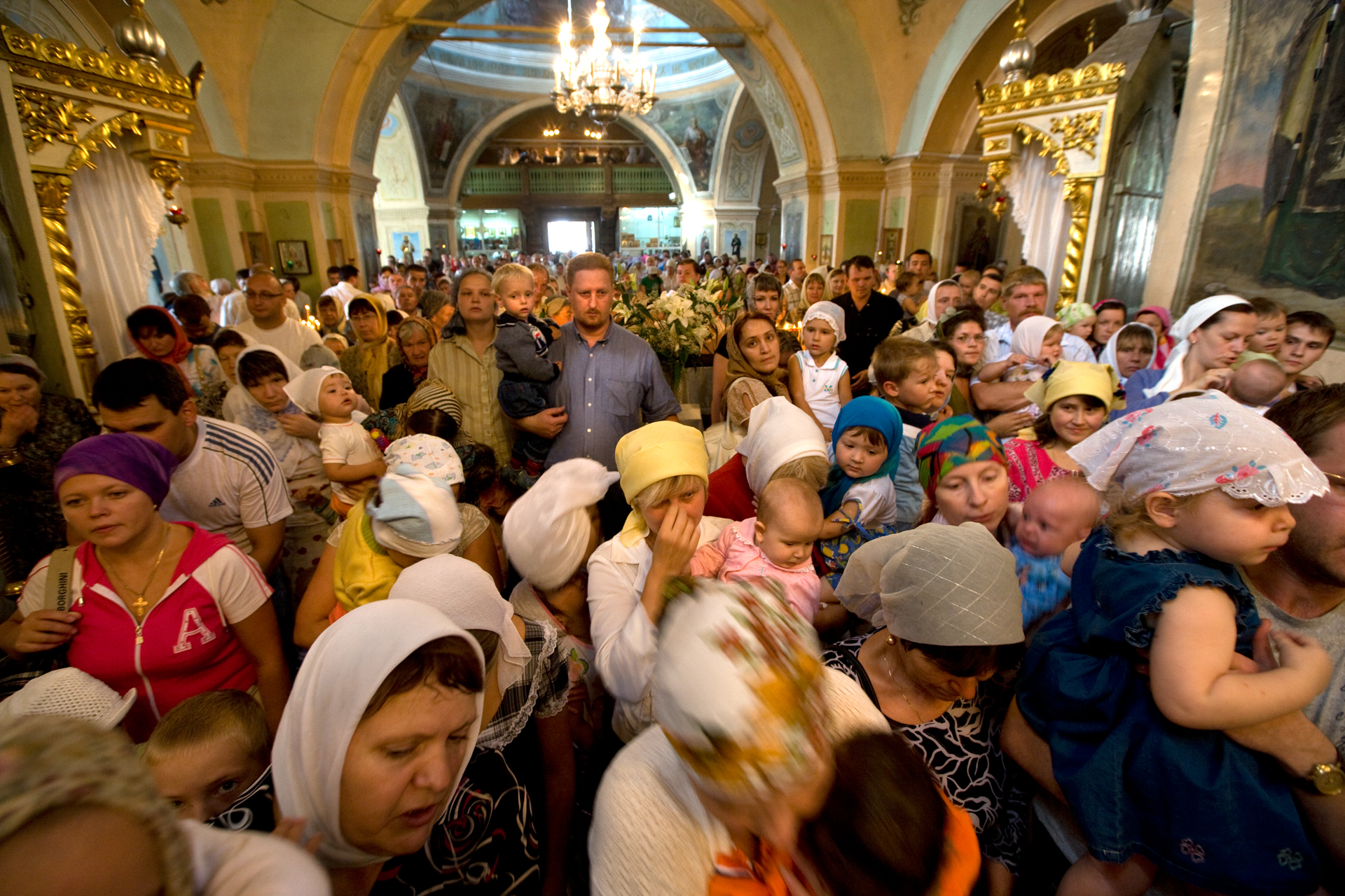 New generations of believers pack into the ornate spaces of Znamensky Cathedral for the feast day of the Transfiguration.  Tyumen, Russia
