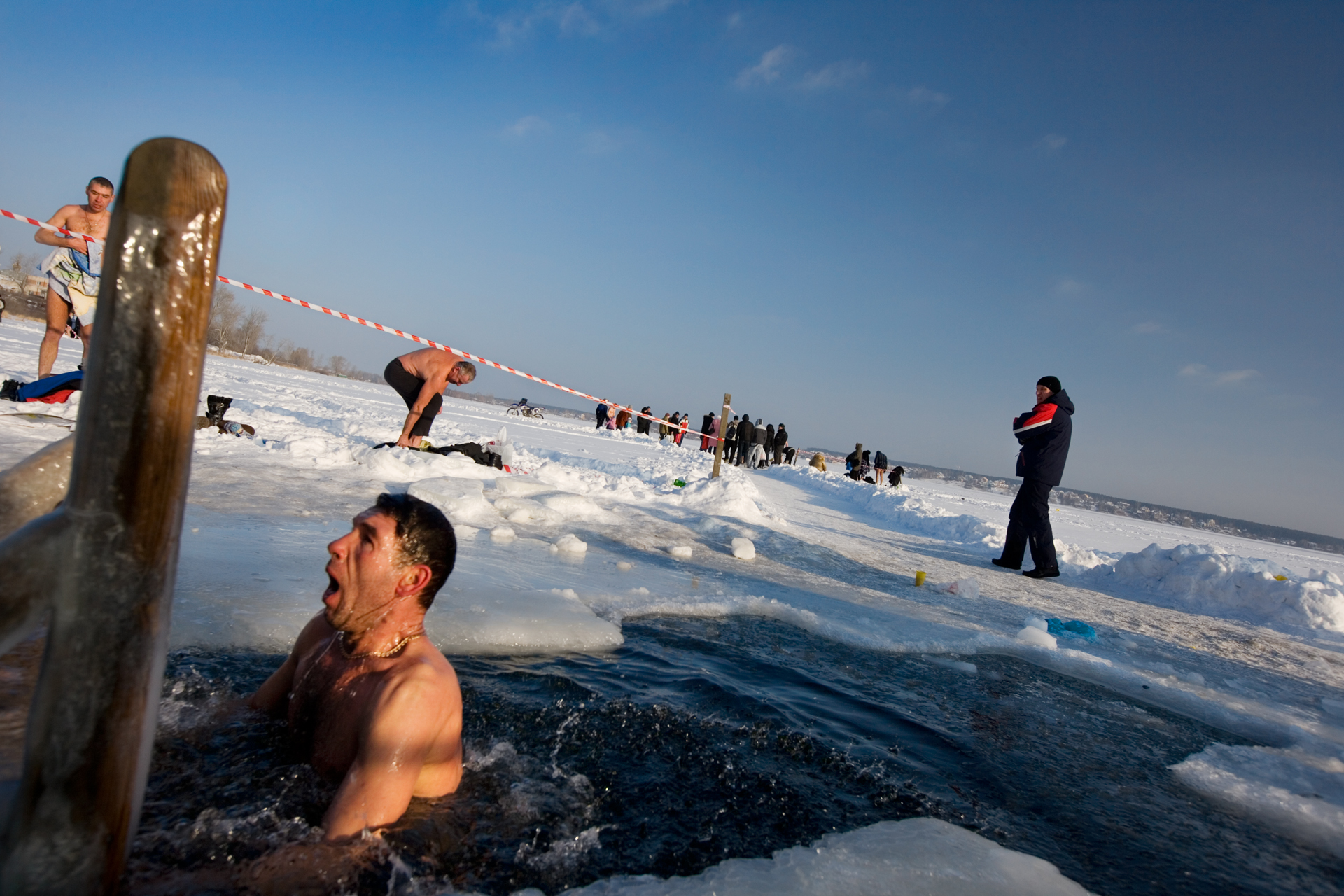 Pious in the extreme, a parishioner gasps after plunging into a cross-shaped hole cut into Lake Shartash at Epiphany.  Yekaterinburg, Russia