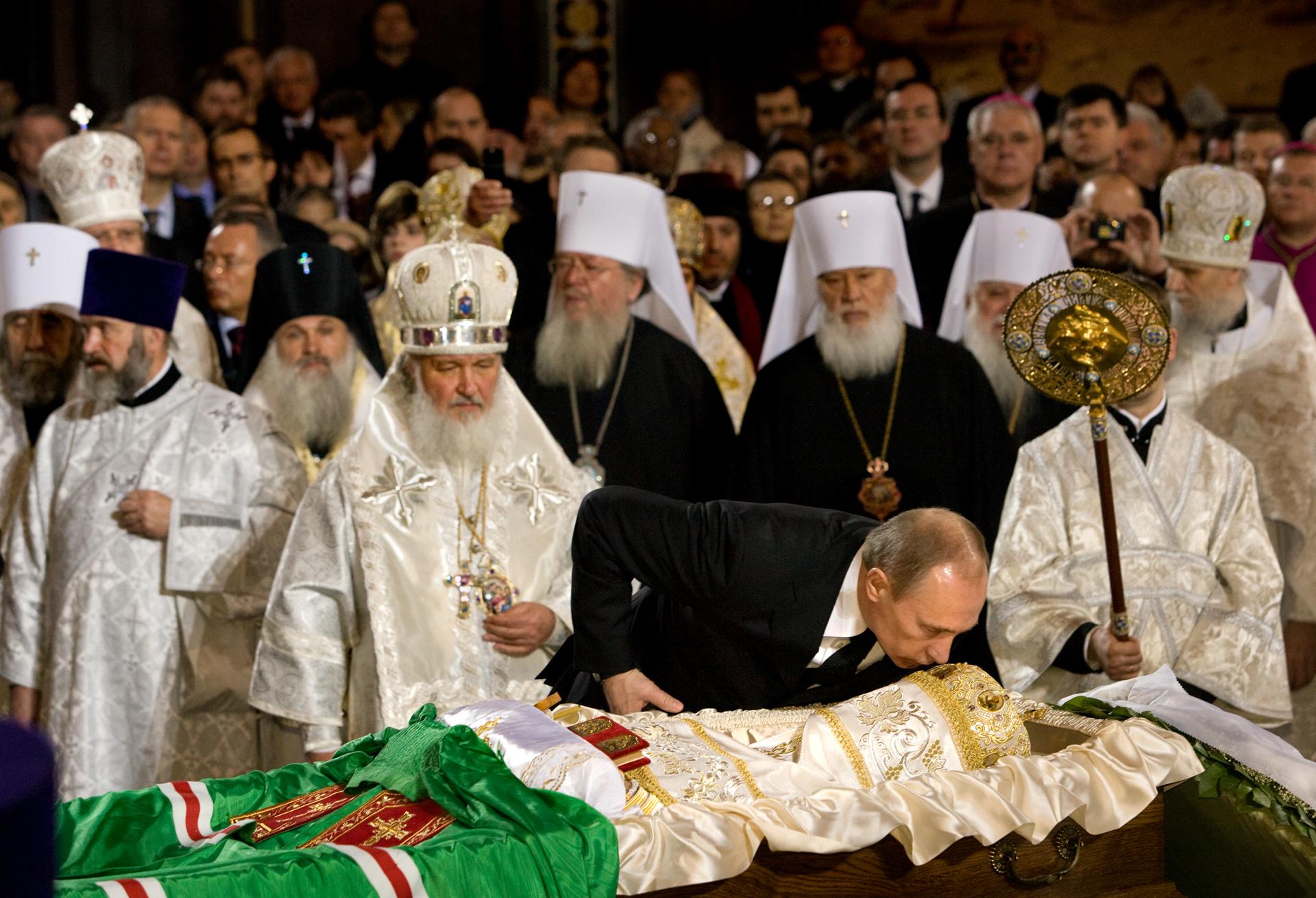 At the funeral of Alexy II, Prime Minister Putin kisses the body of the late patriarch while the successor, Metropolitan Kirill stands close.  Moscow, Russia