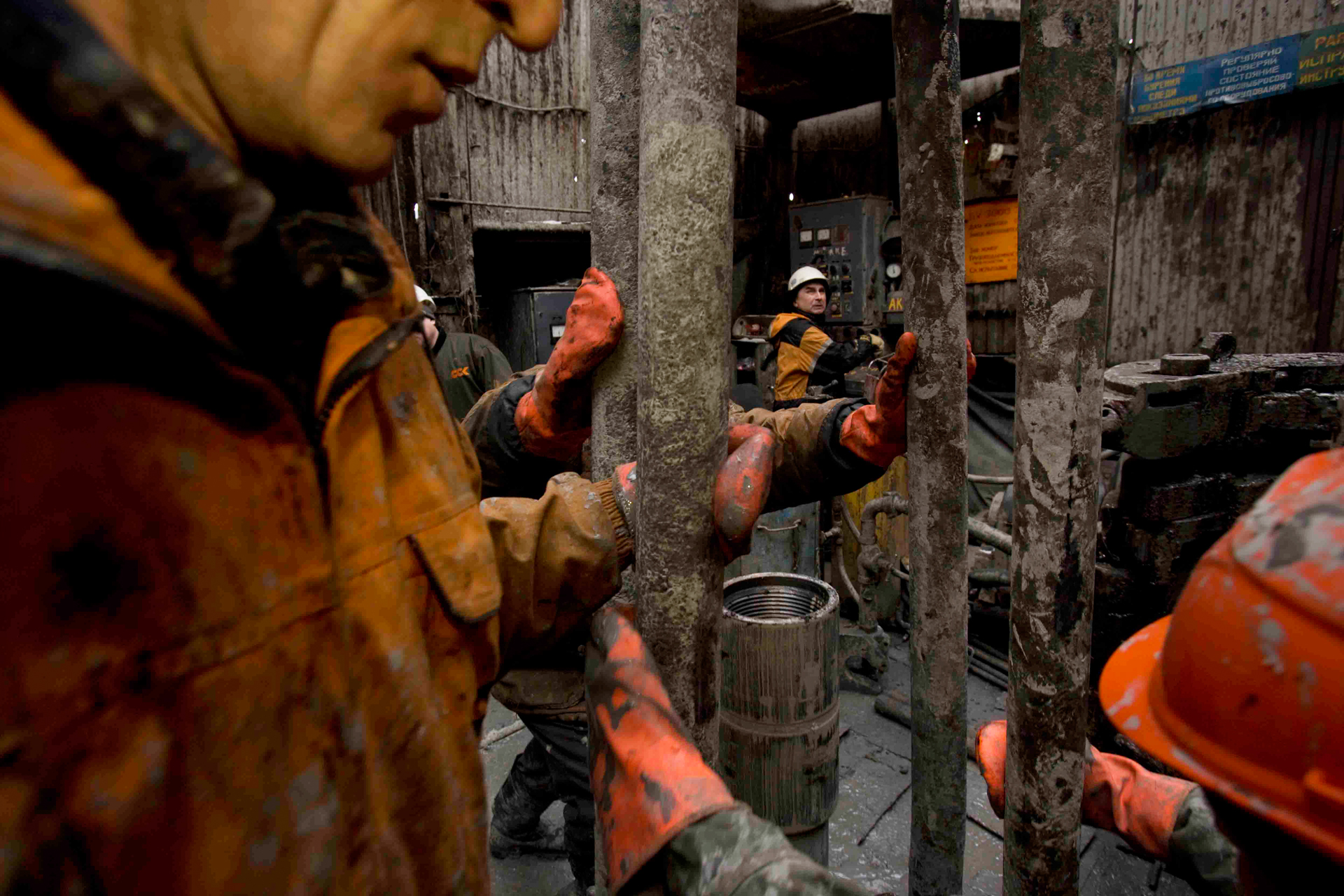 Mud-spattered and cold, oil workers change a drilling pipe. The enormous growth of Russia's oil industry has been fueled by surging world oil prices.  Yuzhno-Priobskoye, Russia