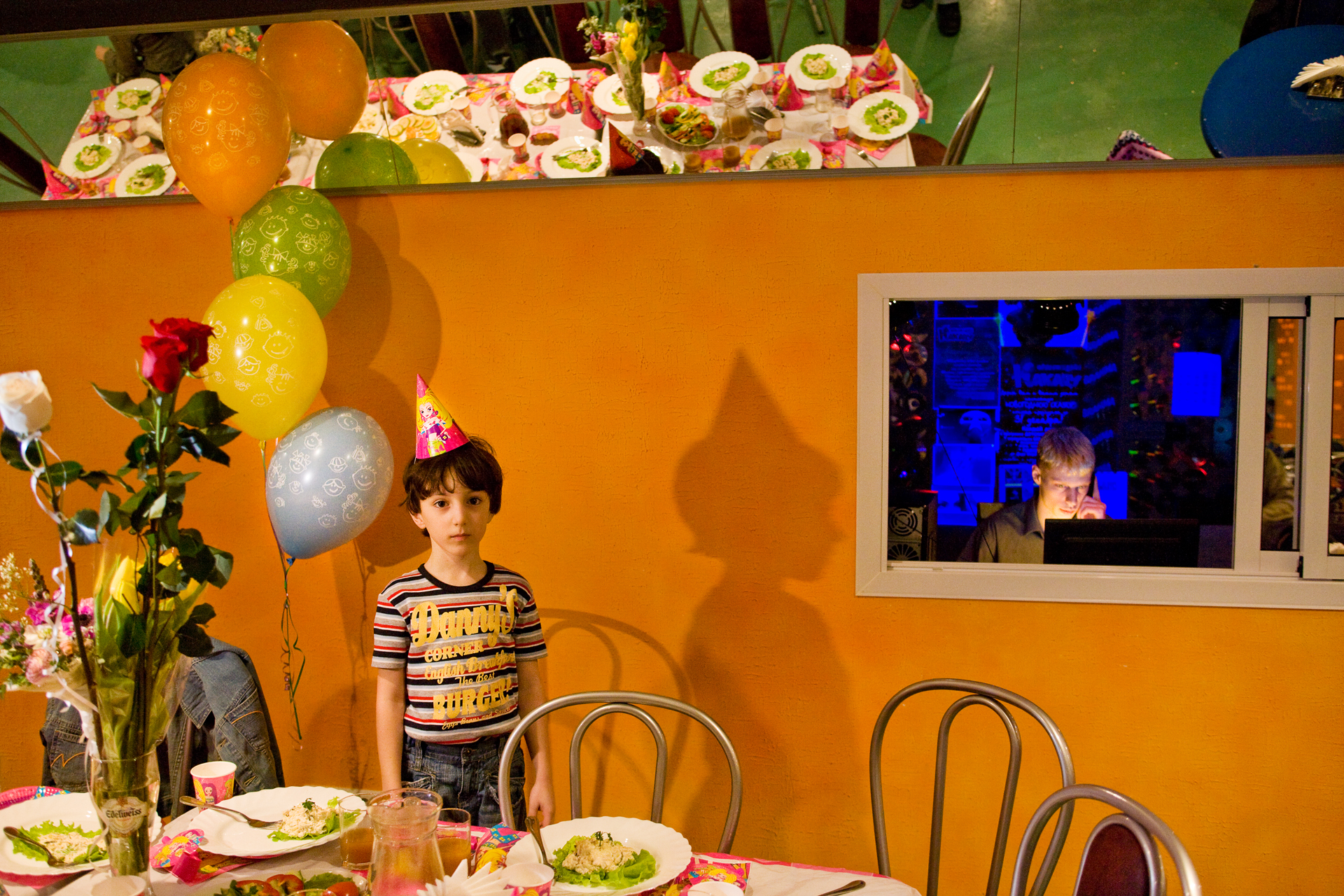 Overwhelmed by a lavish birthday party at the new Orange Parrot Entertainment Center, a young guest pauses during the state-of-the-art celebration.  Surgut, Russia
